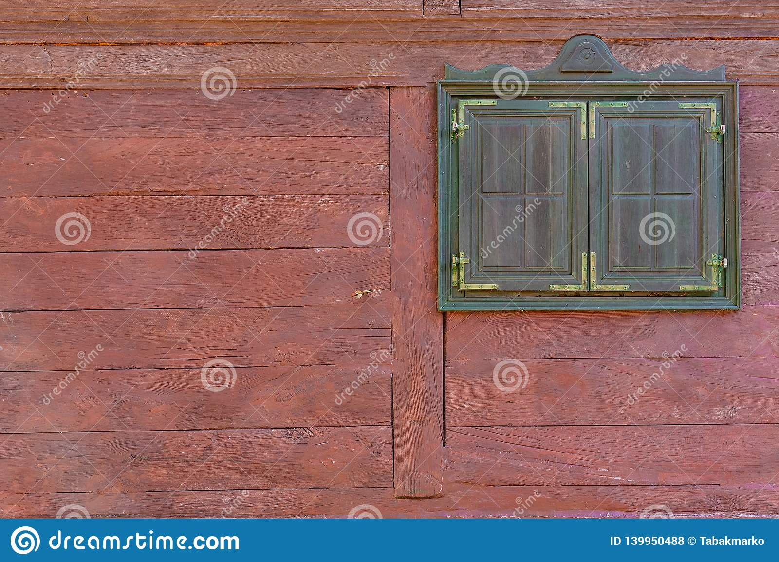 A brown window on a red wooden cabin wall
