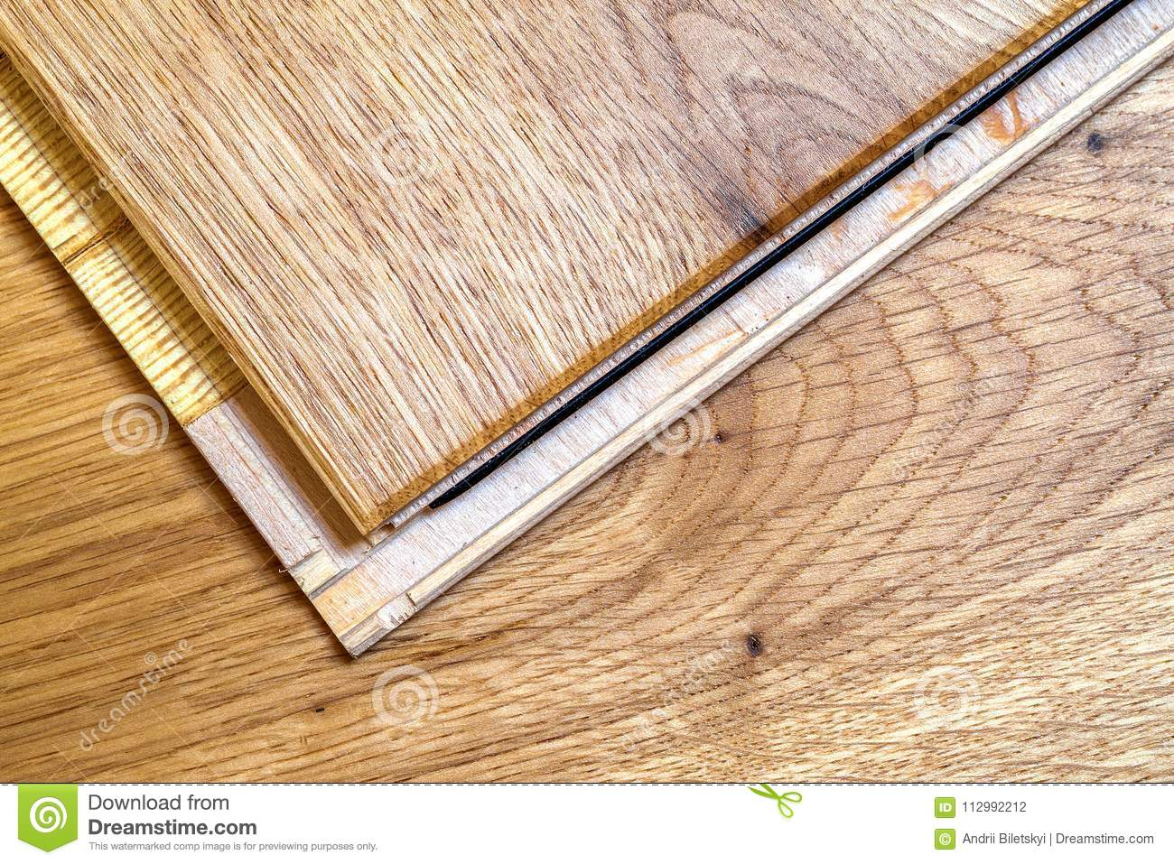 Brown wooden parquet floor planks installation , close up. Carpentry concept.