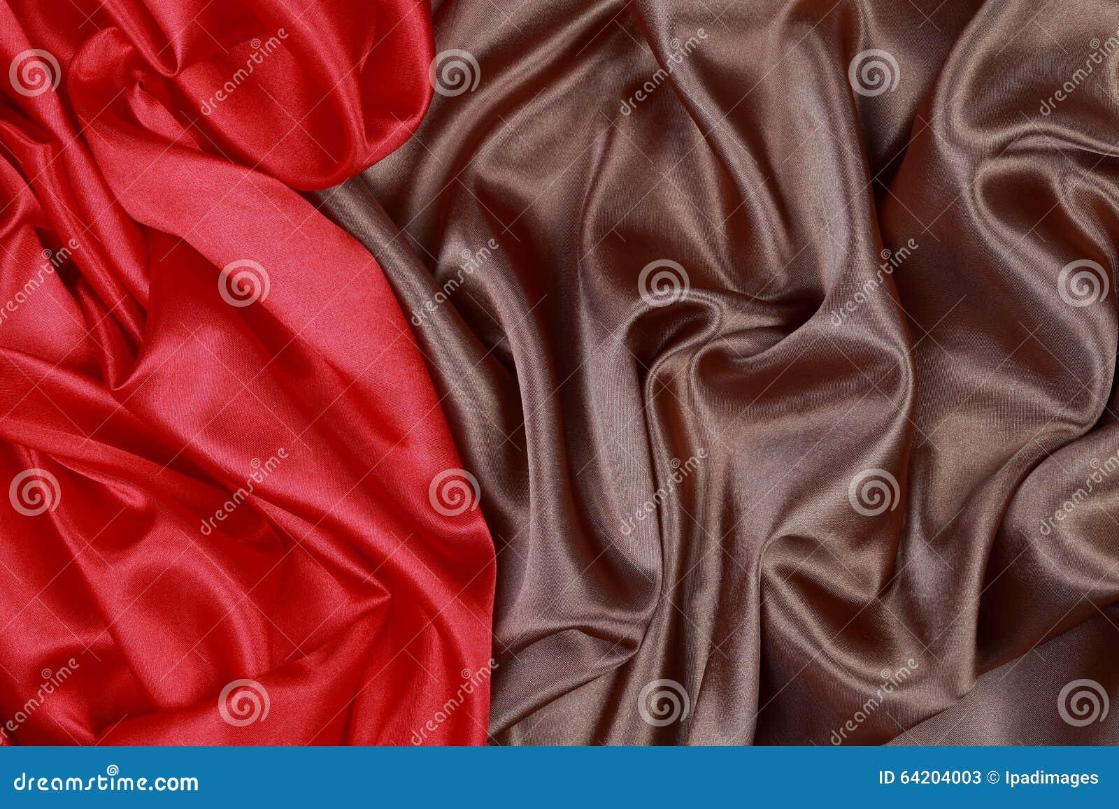 Brown y el paño de seda rojo del satén de dobleces ondulados texturizan el fondo