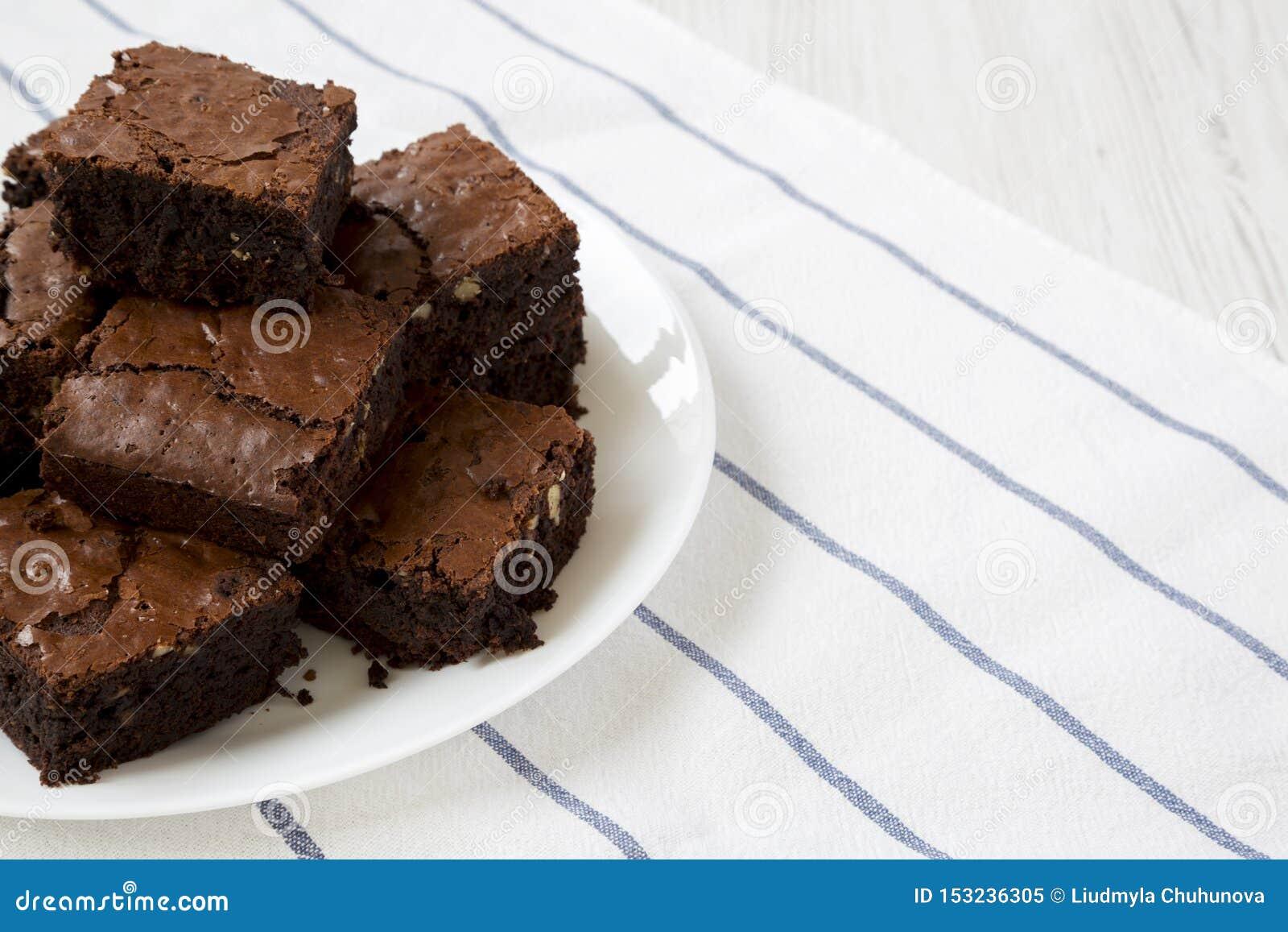 Brownie casalinghi del cioccolato su un piatto bianco, vista laterale Primo piano Copi lo spazio