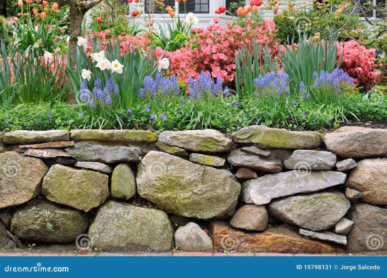 Bruchstein-Wand und bunter Garten