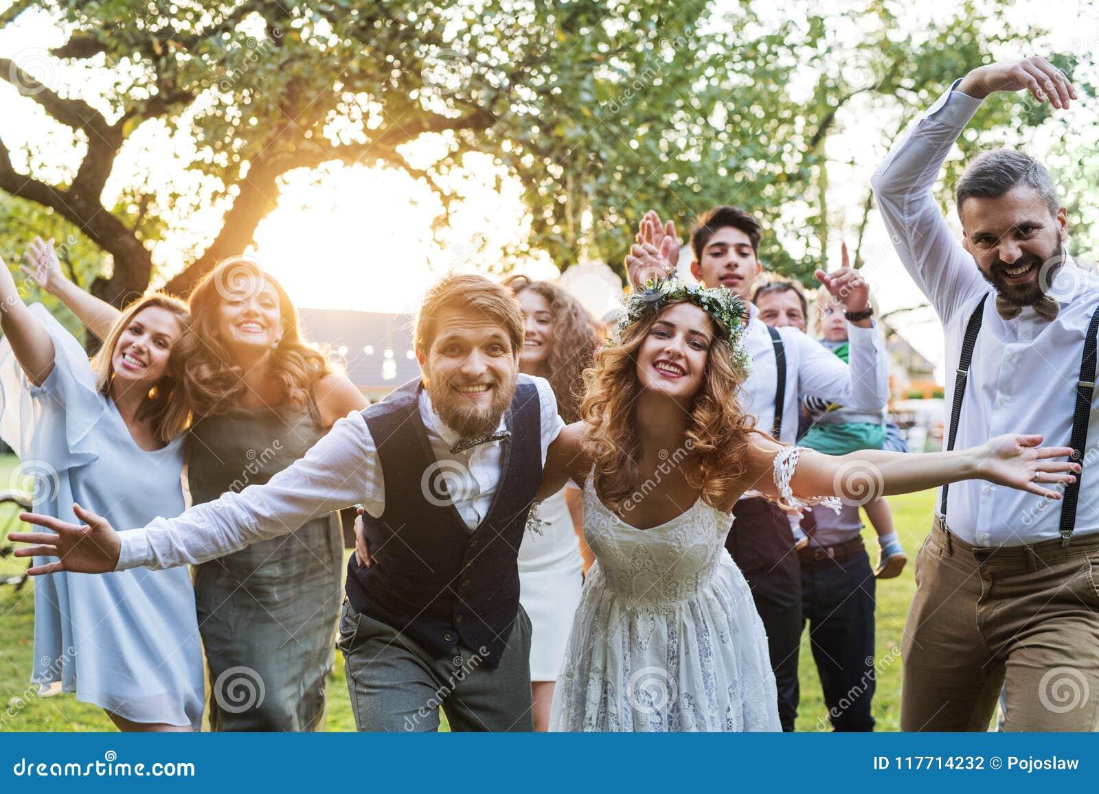 Brud brudgum, gäster som poserar för fotoet på bröllopmottagandet utanför i trädgården