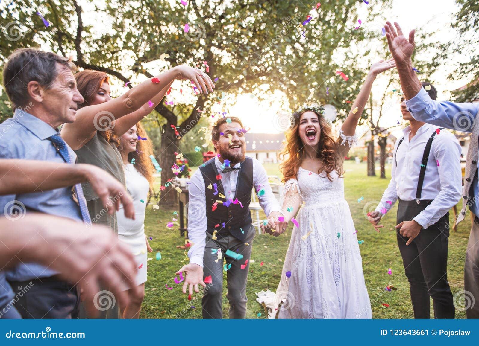 Brud, brudgum och gäster som utanför kastar konfettier på bröllopmottagandet