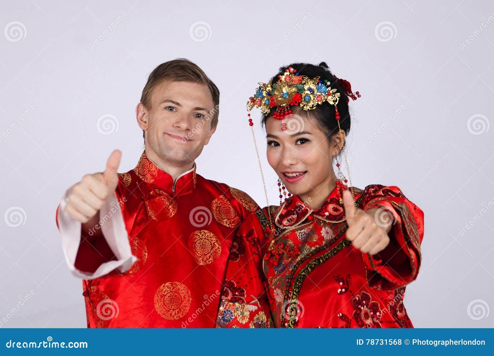 Brud och brudgum för blandat lopp i studion som bär bröllopdräkter för traditionell kines