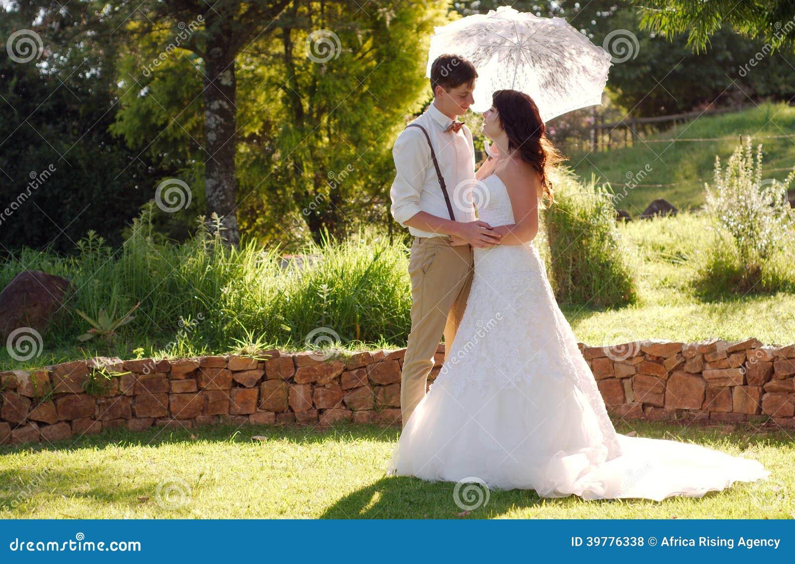 Brud och brudgum i tr dg rds br llop med slags solskydd for Boda en un jardin