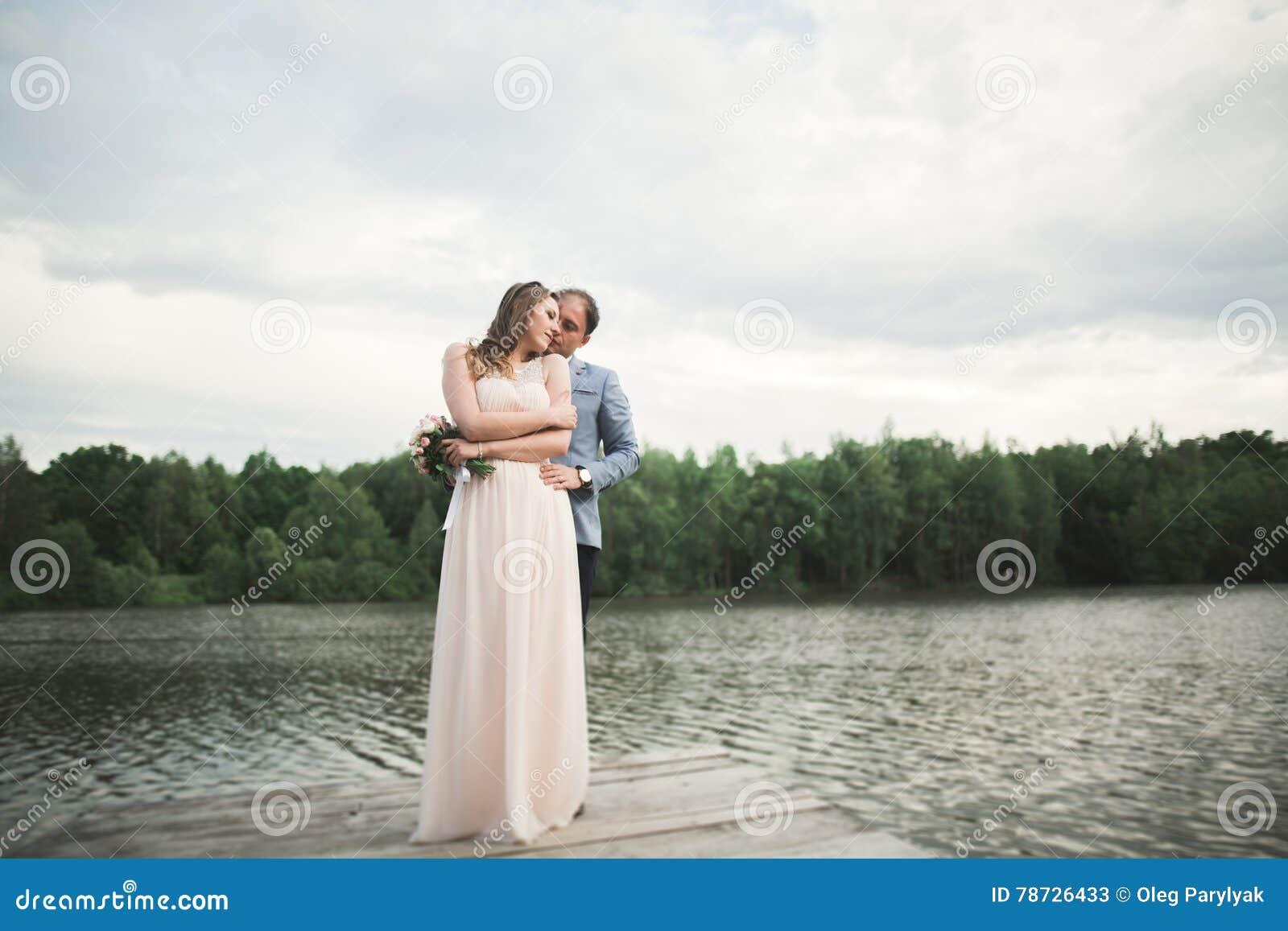 Brud och brudgum som går på floden och att le och att kyssa