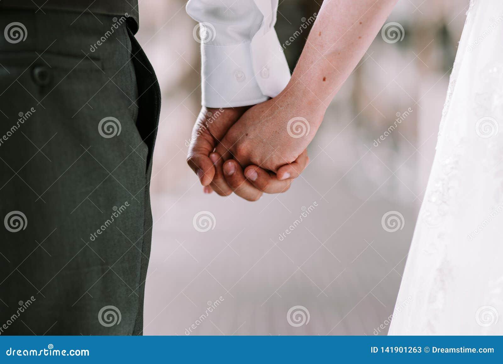 Brud och brudgum som rymmer händer, medan gå