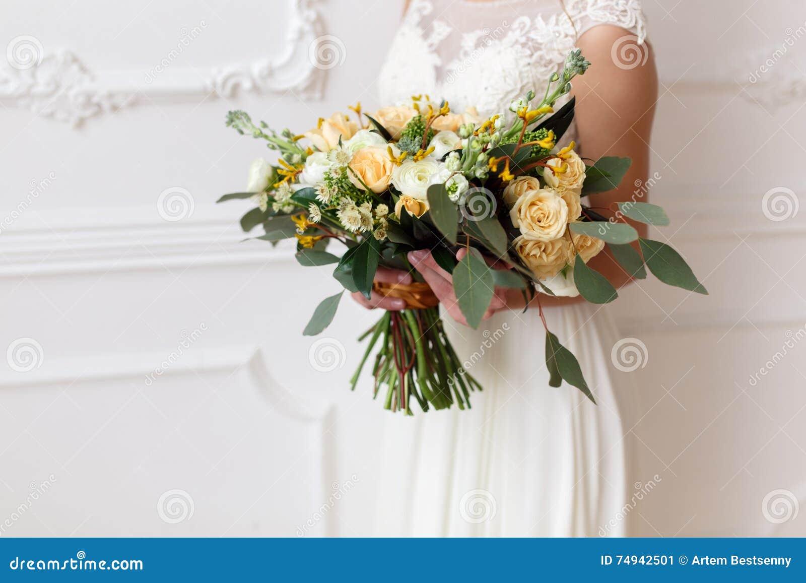 Brud som rymmer en bukett av blommor i en lantlig stil som gifta sig buketten