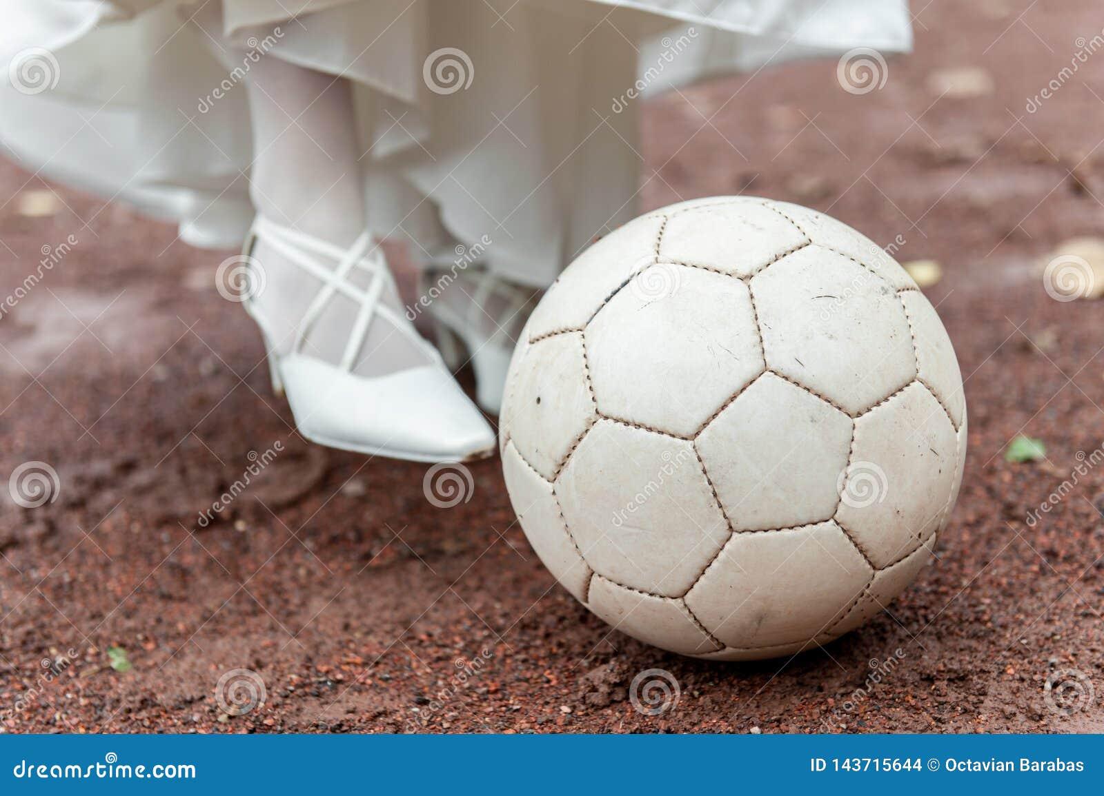 Brud som spelar fotboll med bollen