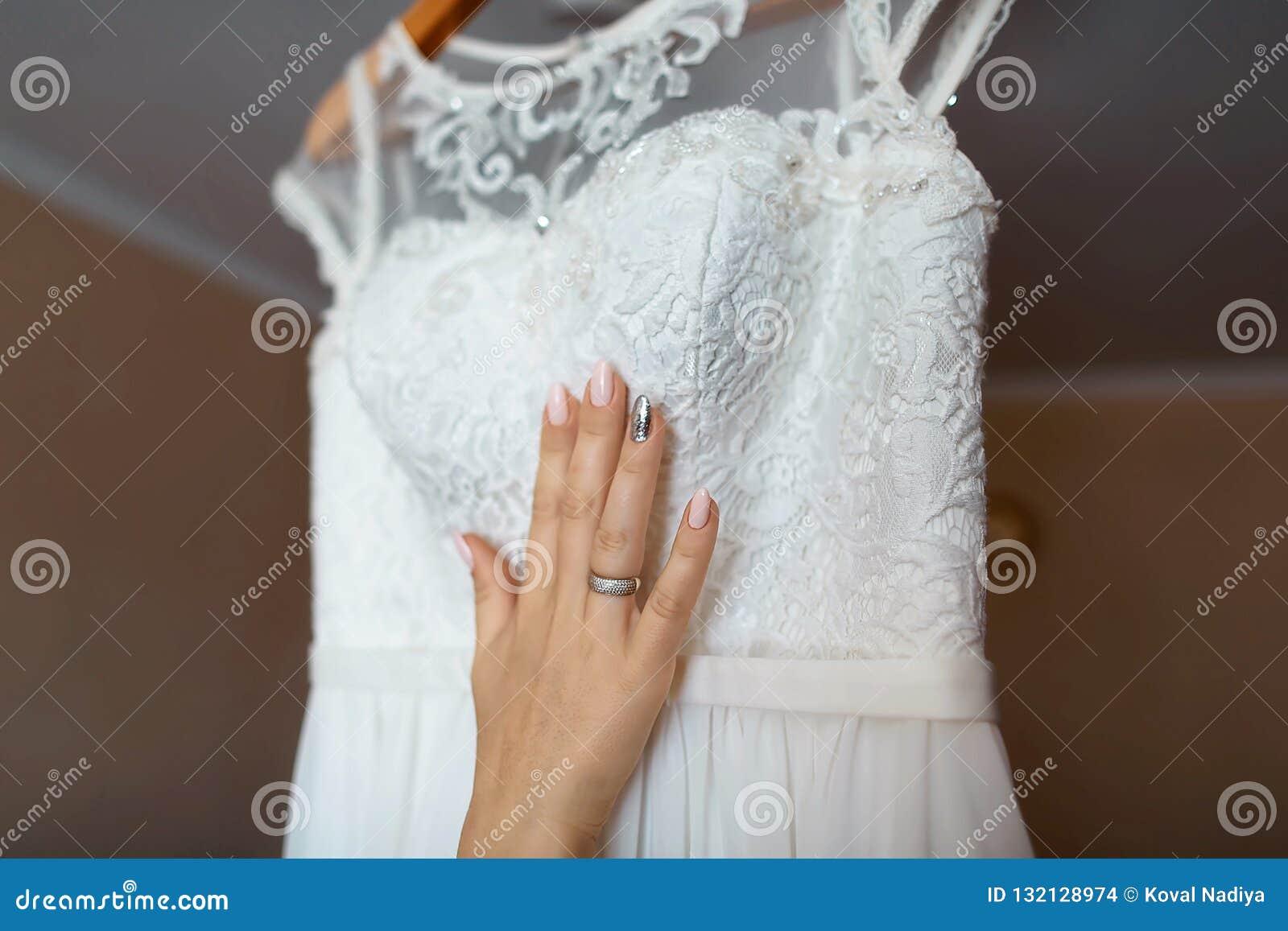 Bruden älskar bröllopsklänningen som är vit snör åt, brudens hand med snör åt och manikyr, morgonbrud