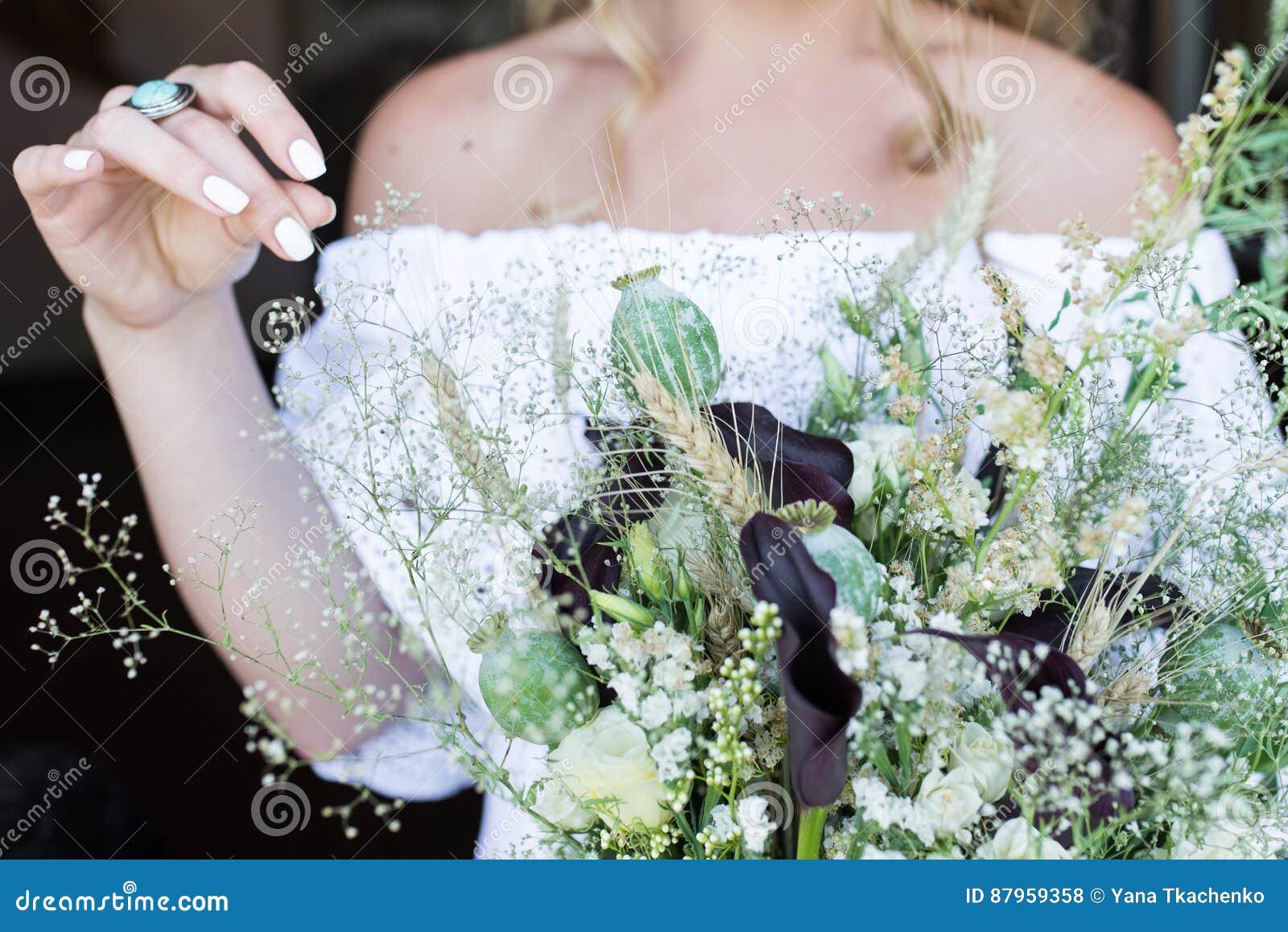 Bruden i den vita bröllopsklänningen rymmer en bröllopbukett med vallmo utomhus-