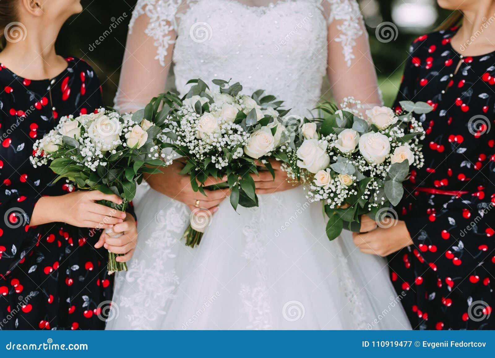 Bruden i en vit snör åt klänningen och två flickor