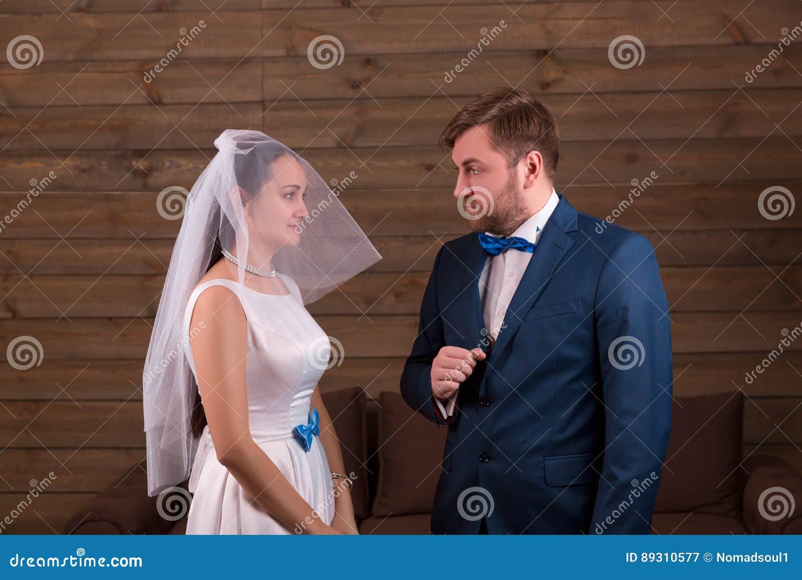 Bruden i klänning och skyler mot brudgum i dräkt