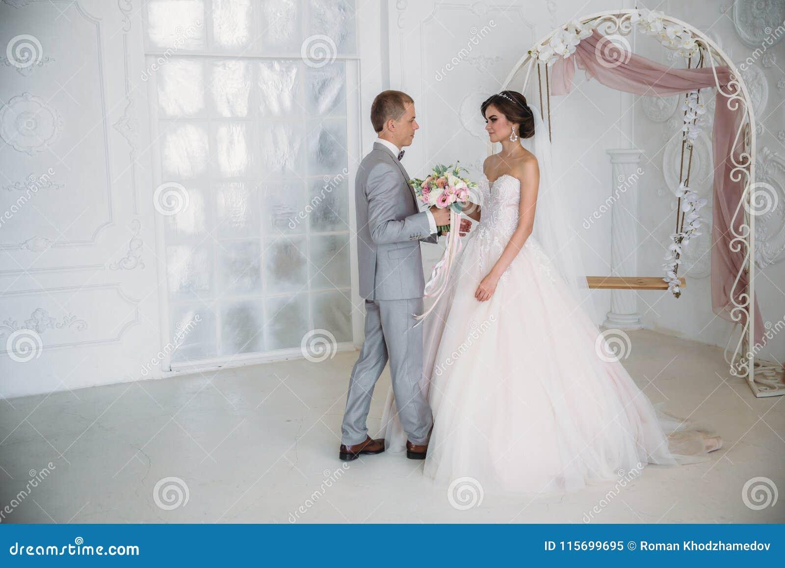 Bruden kramar brudgummen och rymmer en bukett av blommor i hennes händer Ett härligt par av nygifta personer på en bröllopdag