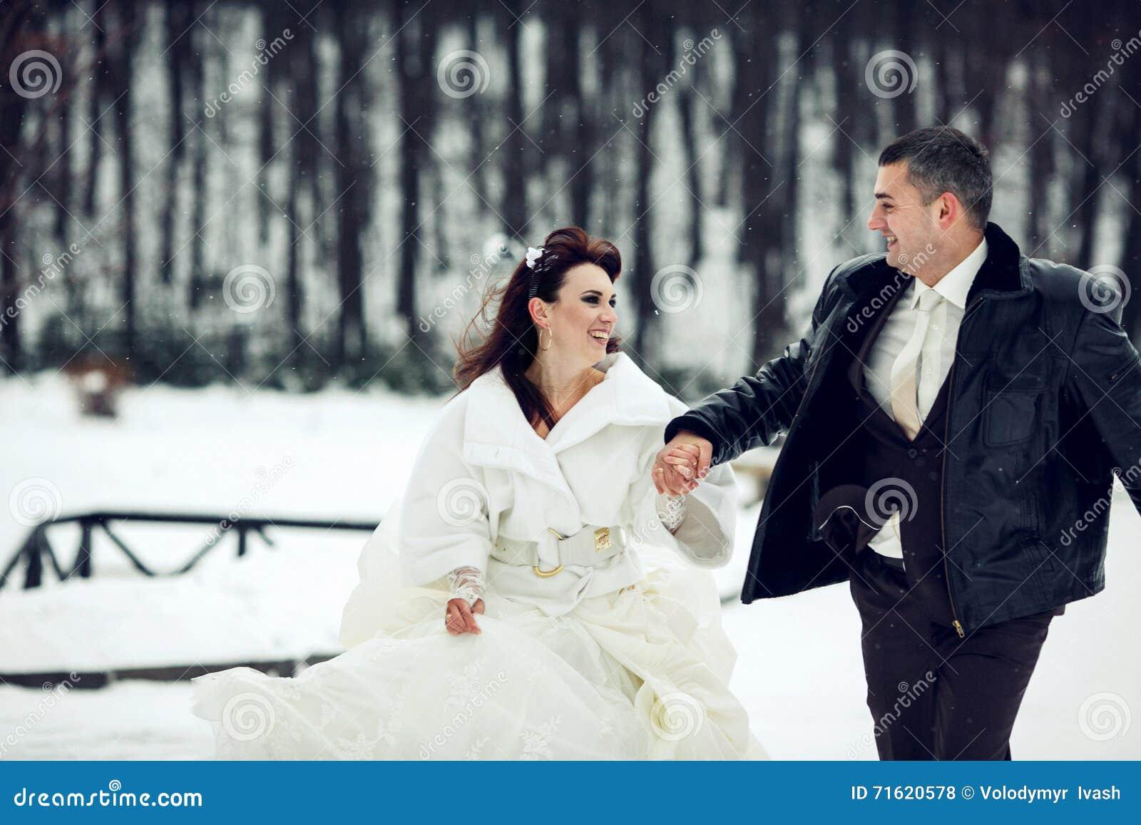 Bruden och brudgummen har gyckel som stöter ihop med en parkera i snöweathen