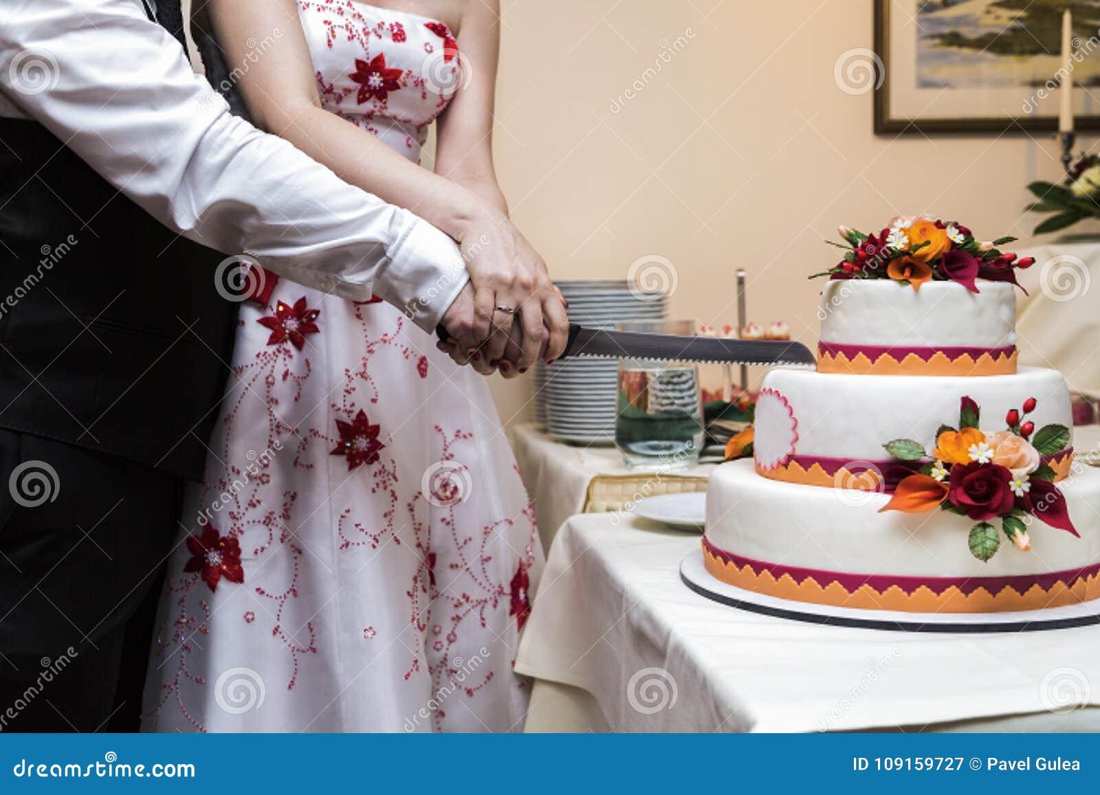 Bruden och brudgummen klipper med den vita stora härliga bröllopstårtan för kniven