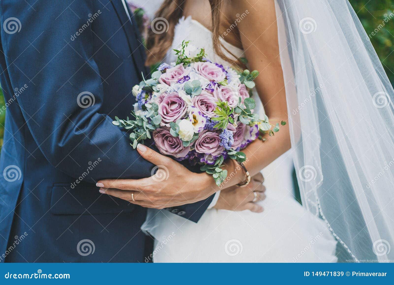 Bruden och brudgummen rymmer en br?llopbukett