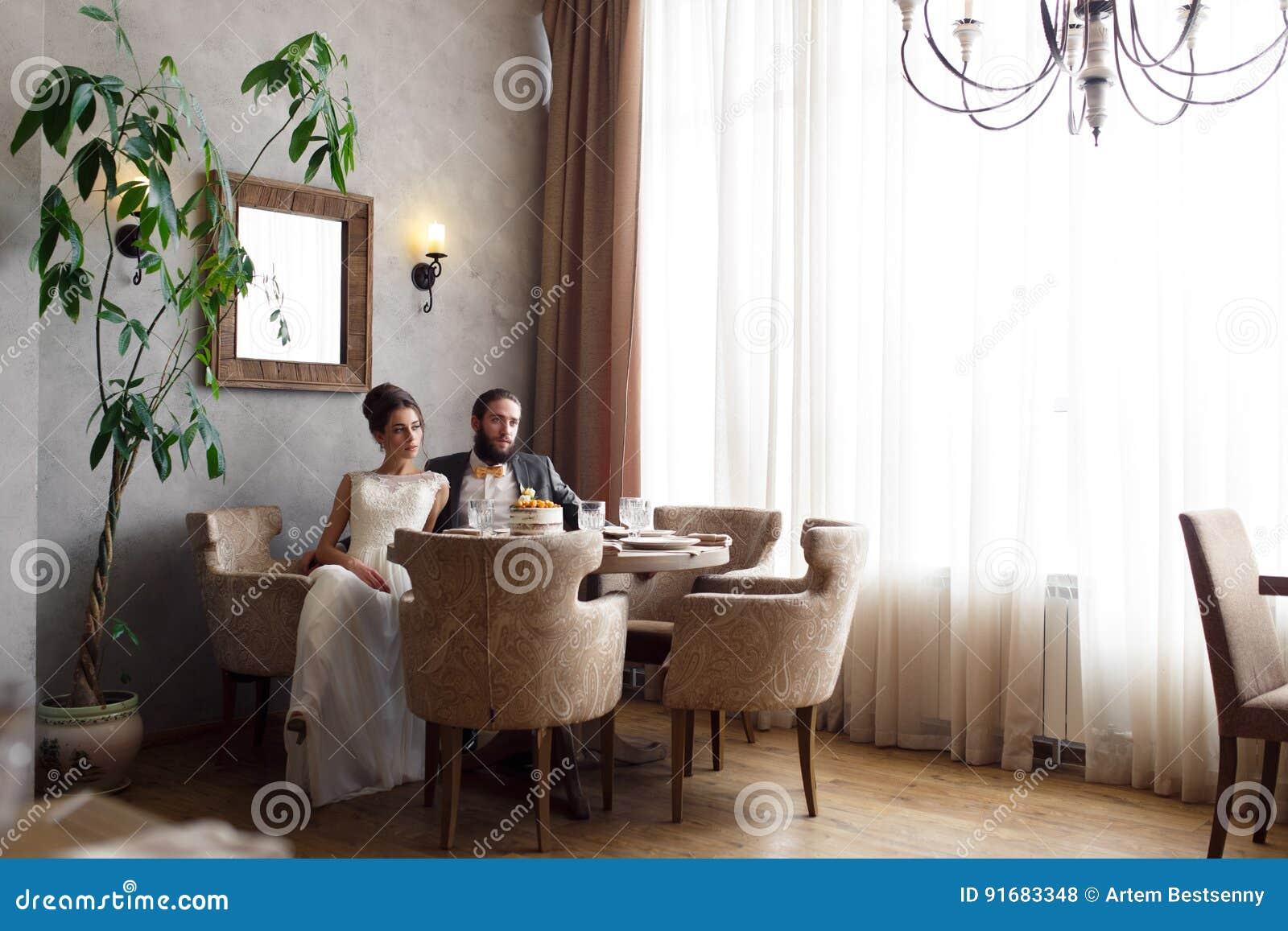 Bruden och brudgummen sitter i fåtöljer på tabellen i en härlig ljus korridor
