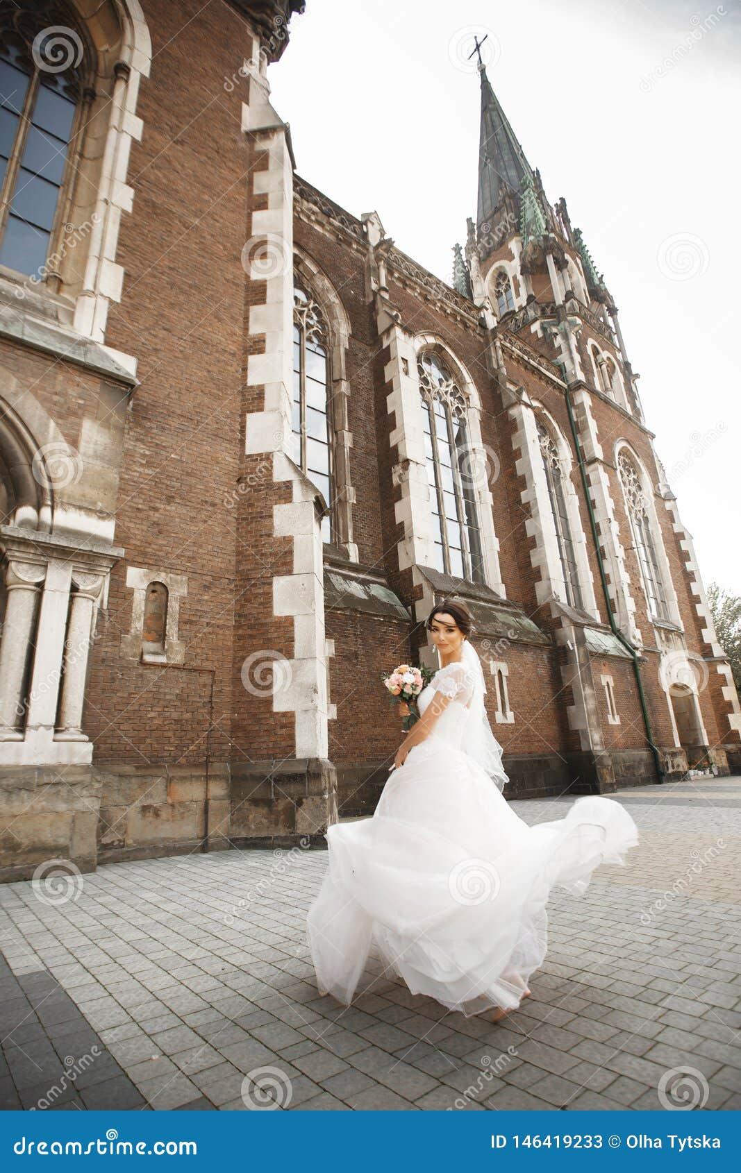 Bruden på går nära väggen av den gamla gotiska kyrkan