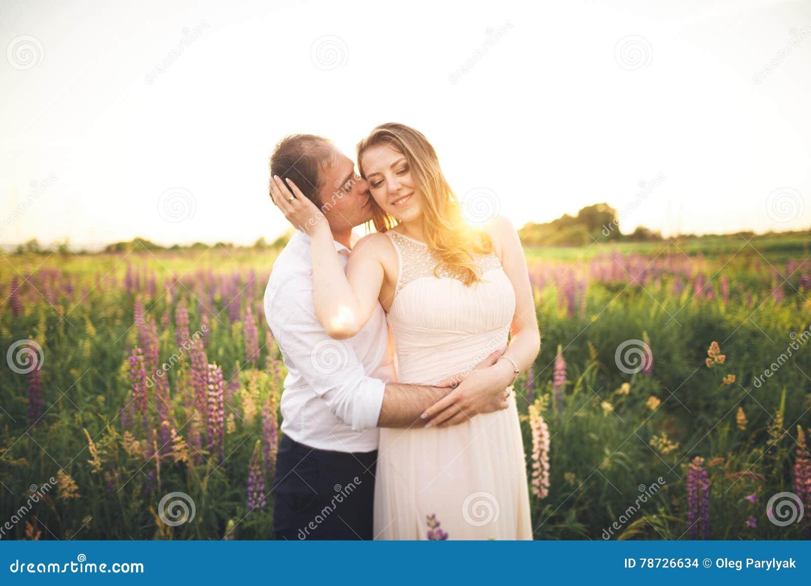 Bruden rymmer brudgummens hals, medan han kysser henne i strålarna av solnedgången