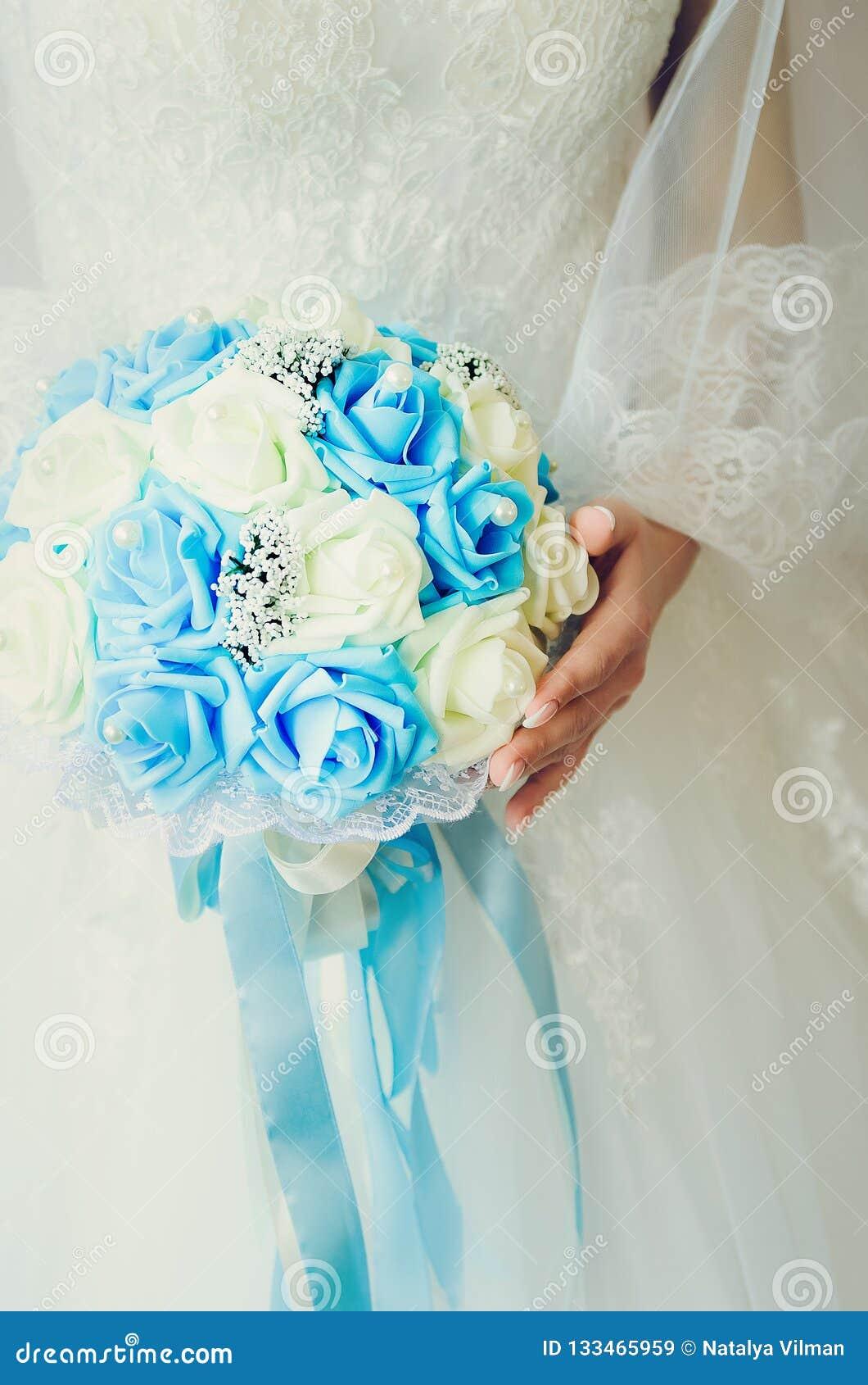 Bruden rymmer en bukett av rosor kläderklänningen viker fragmentbröllopwhite