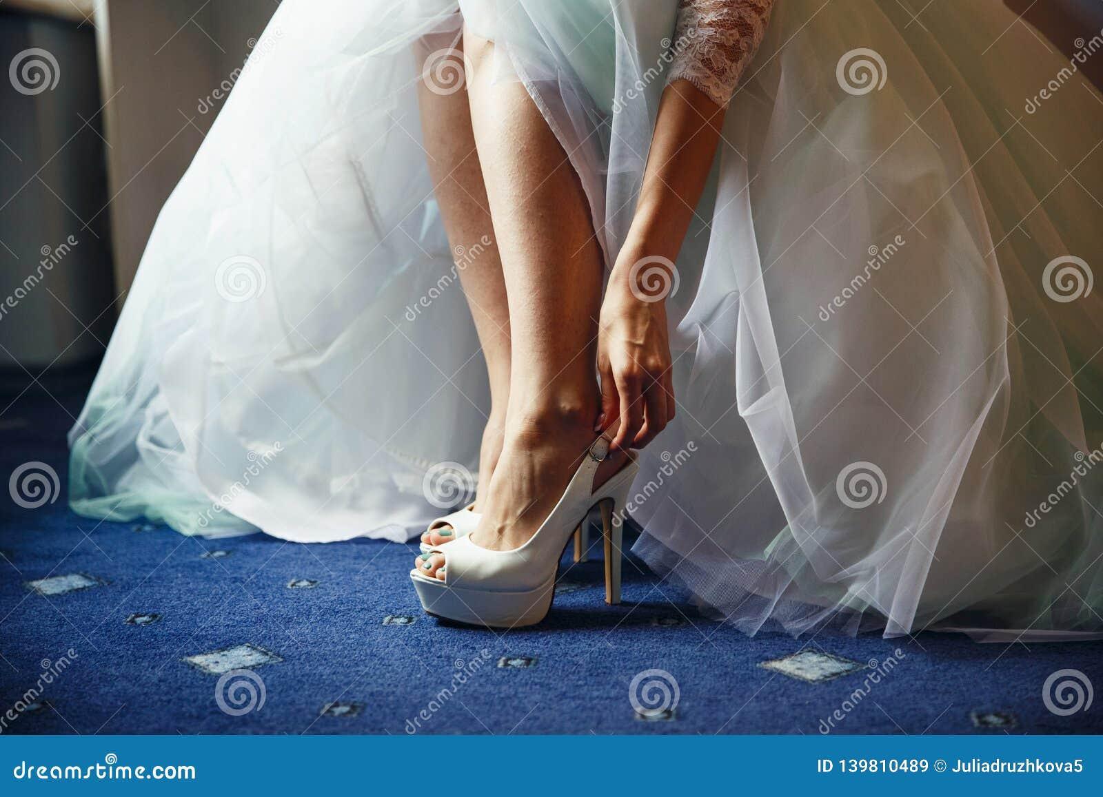 Bruden sätter på vita skor i förberedelsen för bröllopet
