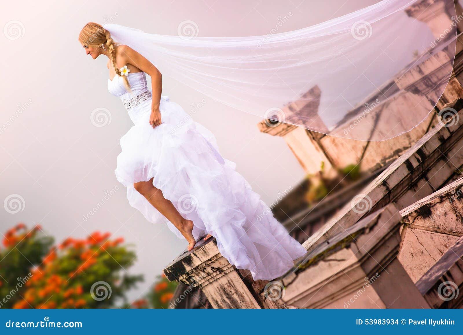 Bruden som bär i härlig klänning och, skyler