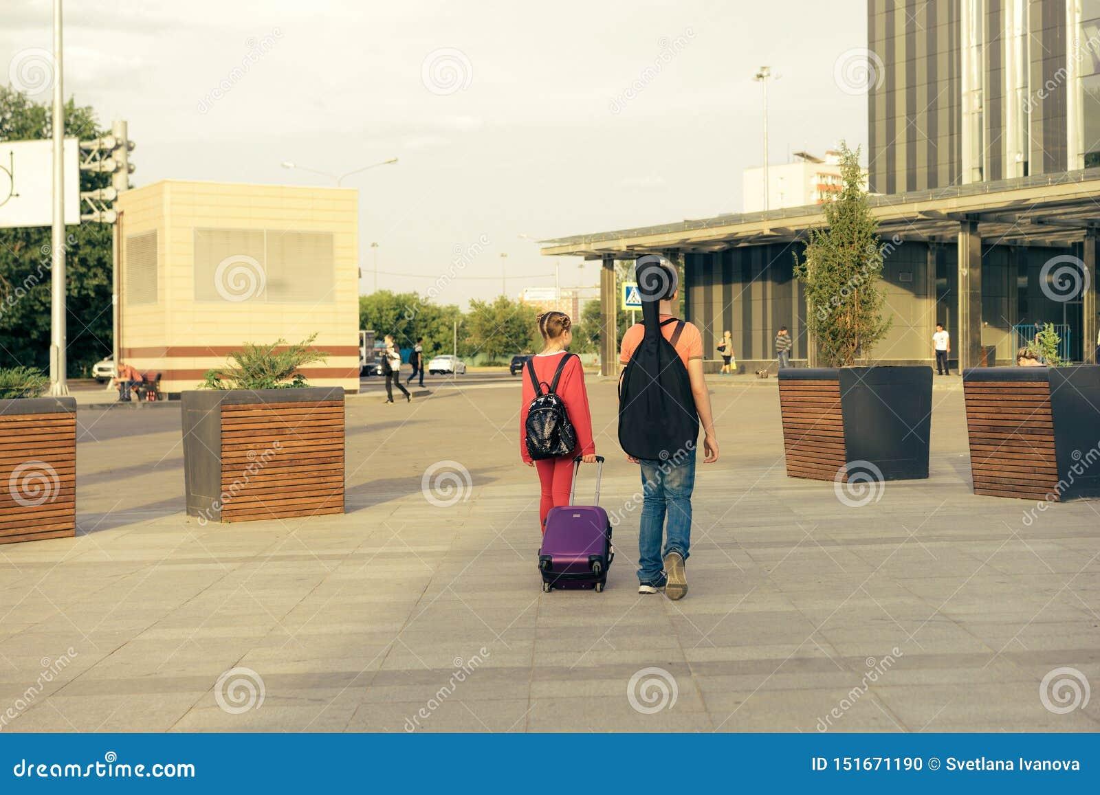 Bruder und Schwester mit einem Koffer, einem Rucksack und einer Gitarre gehen zur Station