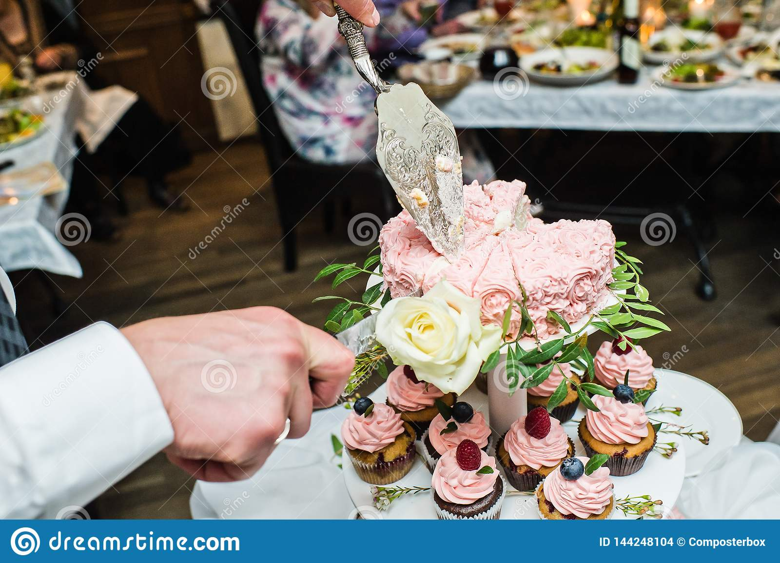 Brudgummen klipper den rosa bröllopstårtan