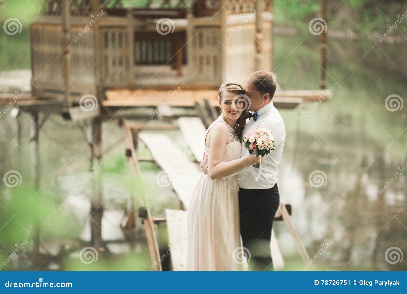 Brudgummen kysser brudens panna, medan hon lutar till honom som ler