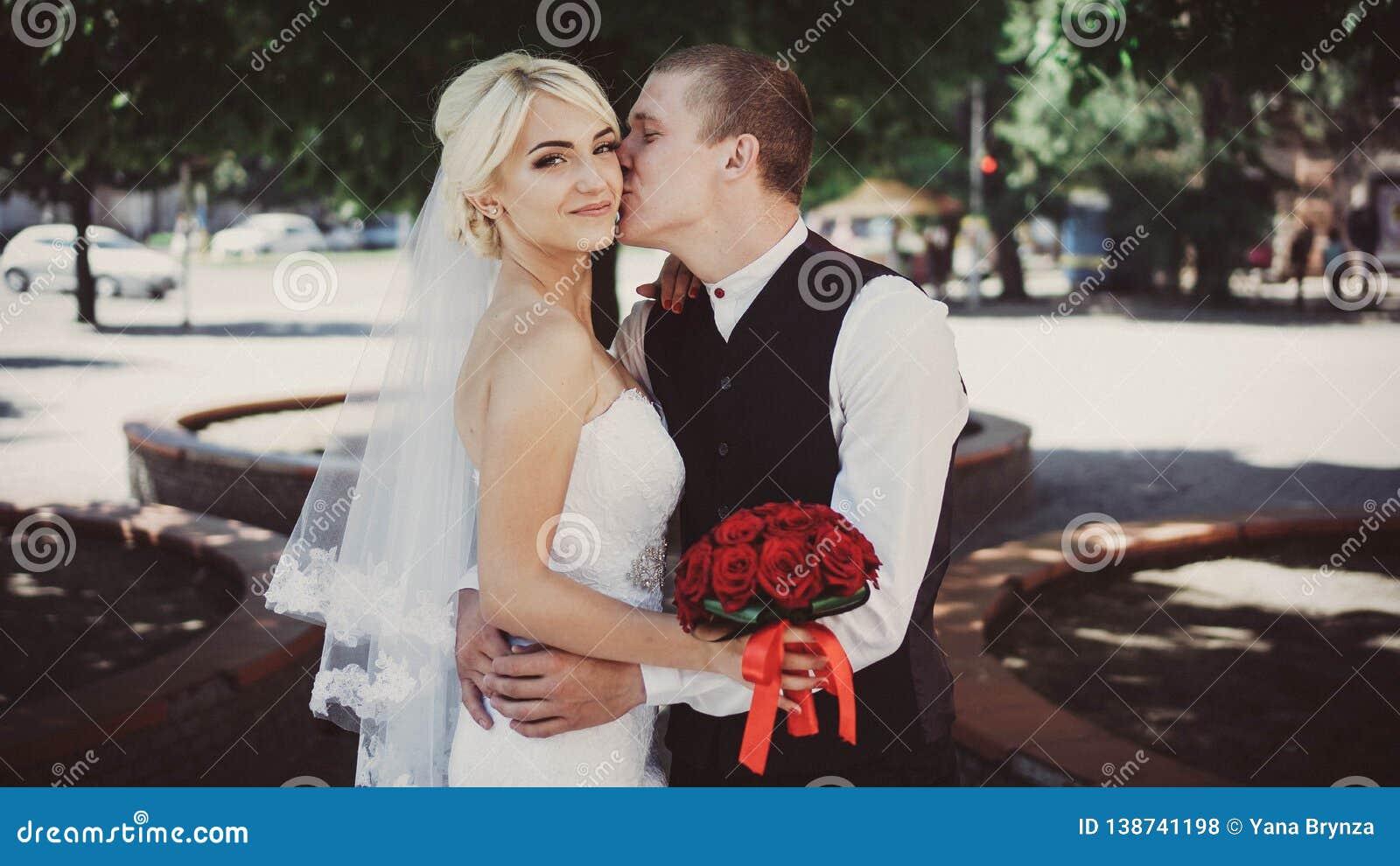 Brudgummen omfamnar och kysser bruden på kinden