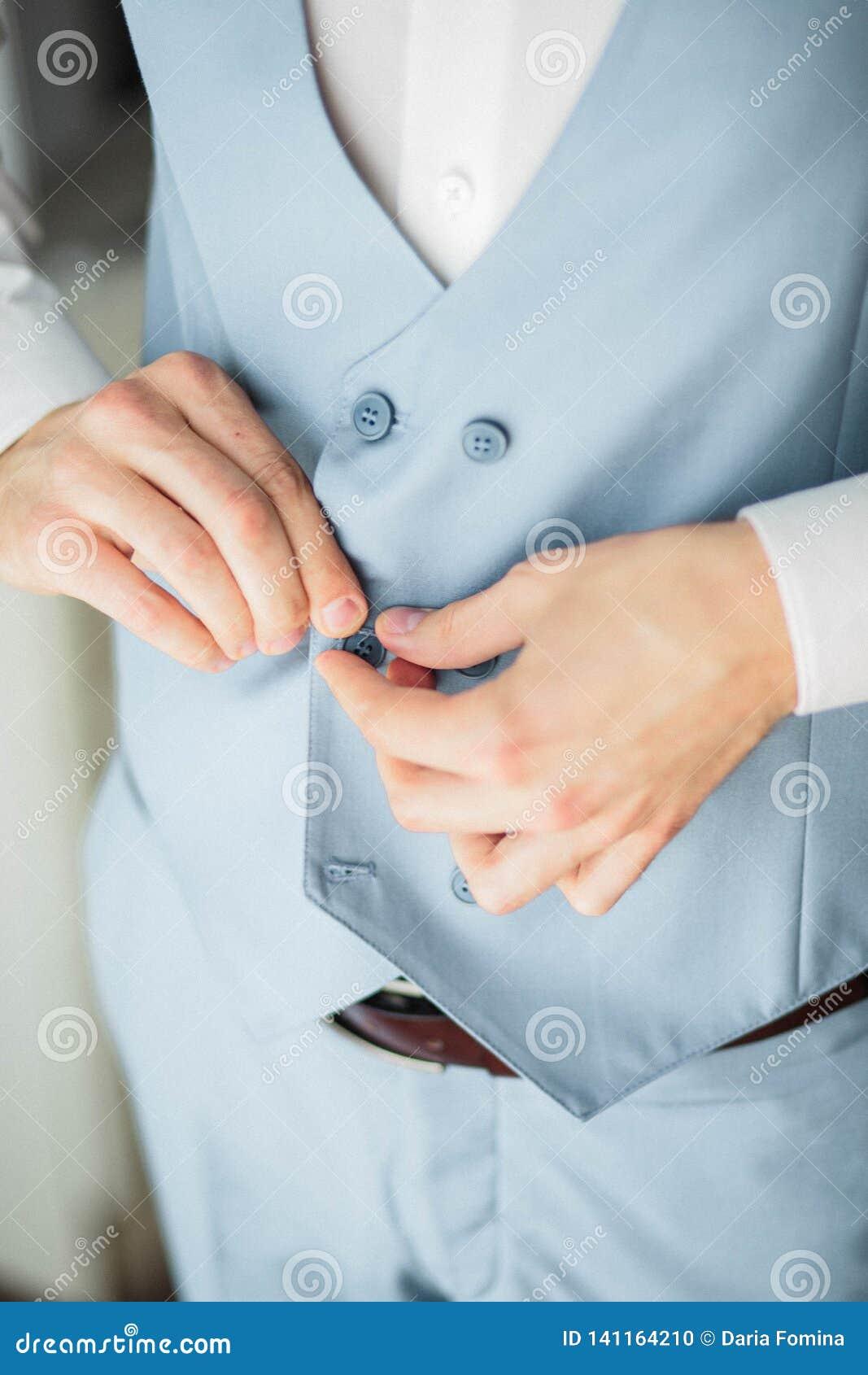 Brudgummorgonförberedelse, stilig brudgum som får klädd