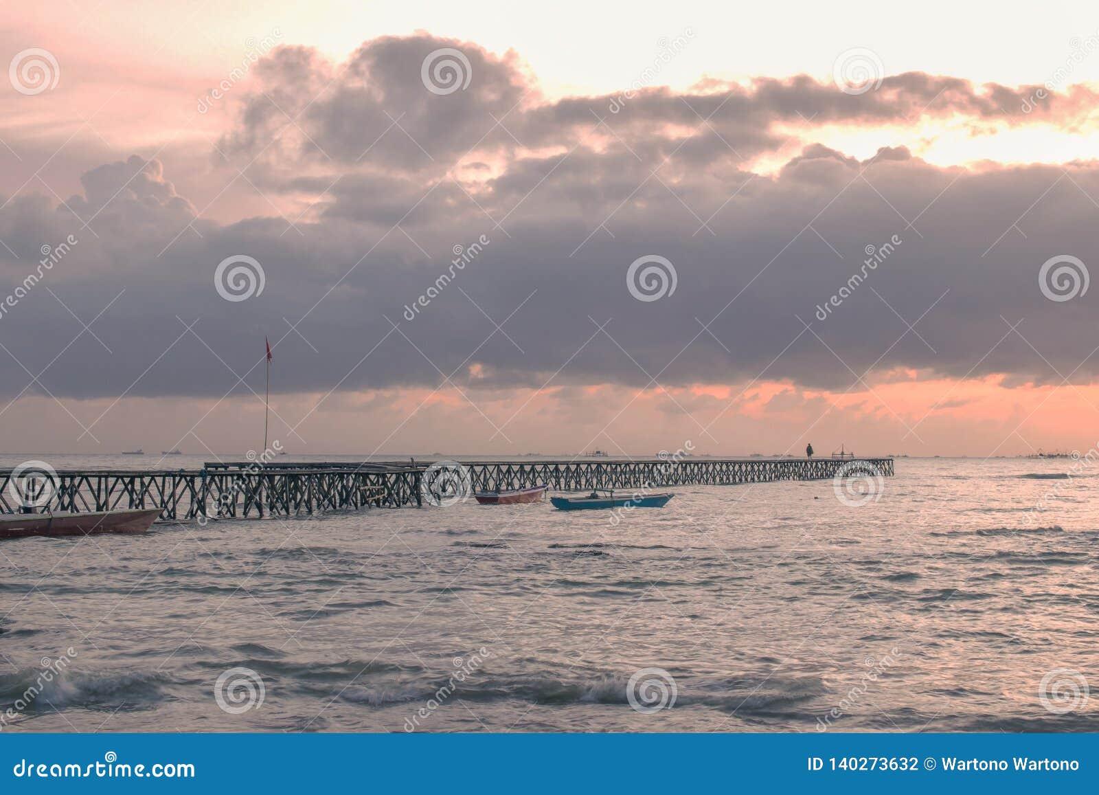 Brug van pijler in het strand bij zonsondergang