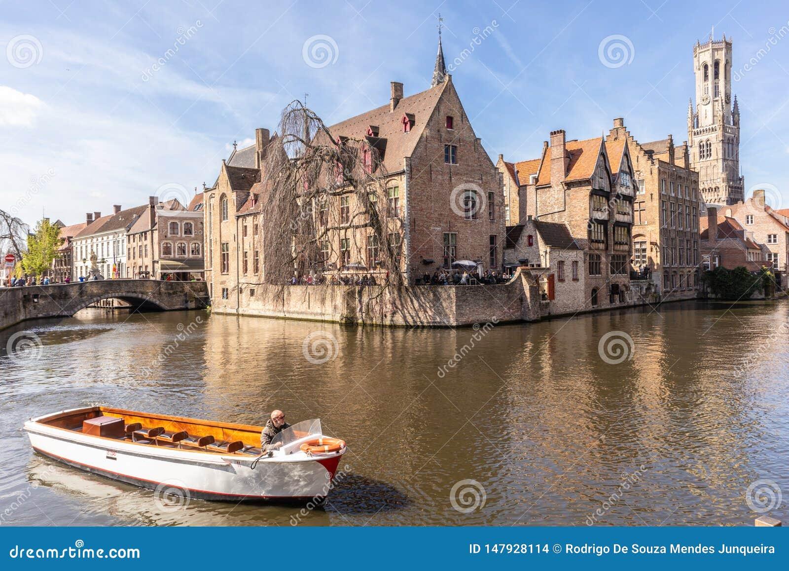 Bruges Belgien - APRIL 05, 2019: Turnera fartyget som tar turister till och med den h?rliga staden av Bruges vid kanalen