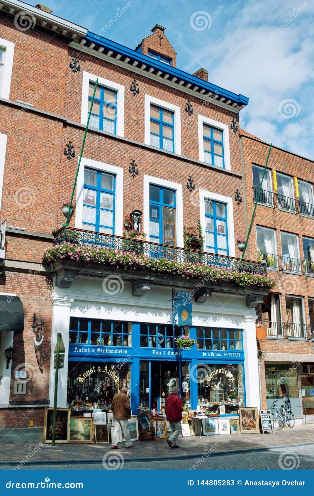 Bruges Belgien - Augusti 2010: Sikten av en byggnad som inhyser 'Dag antikviteten för en Zonne ', shoppar