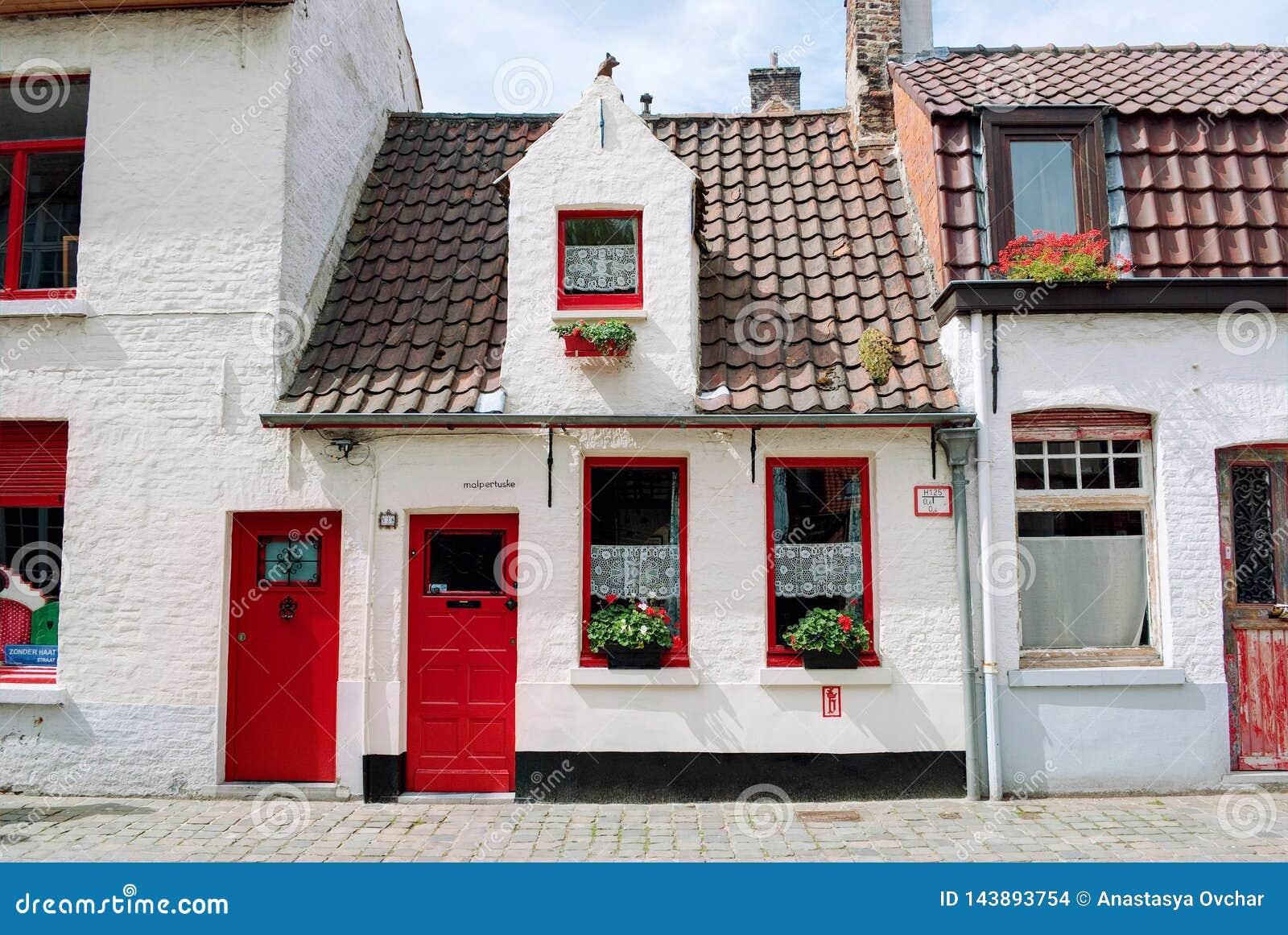 Bruges Belgien - Augusti 2010: Små pittoreska vita hus med röda dörrar, röda fönsterramar, röda blommor och röda taktegelplattor
