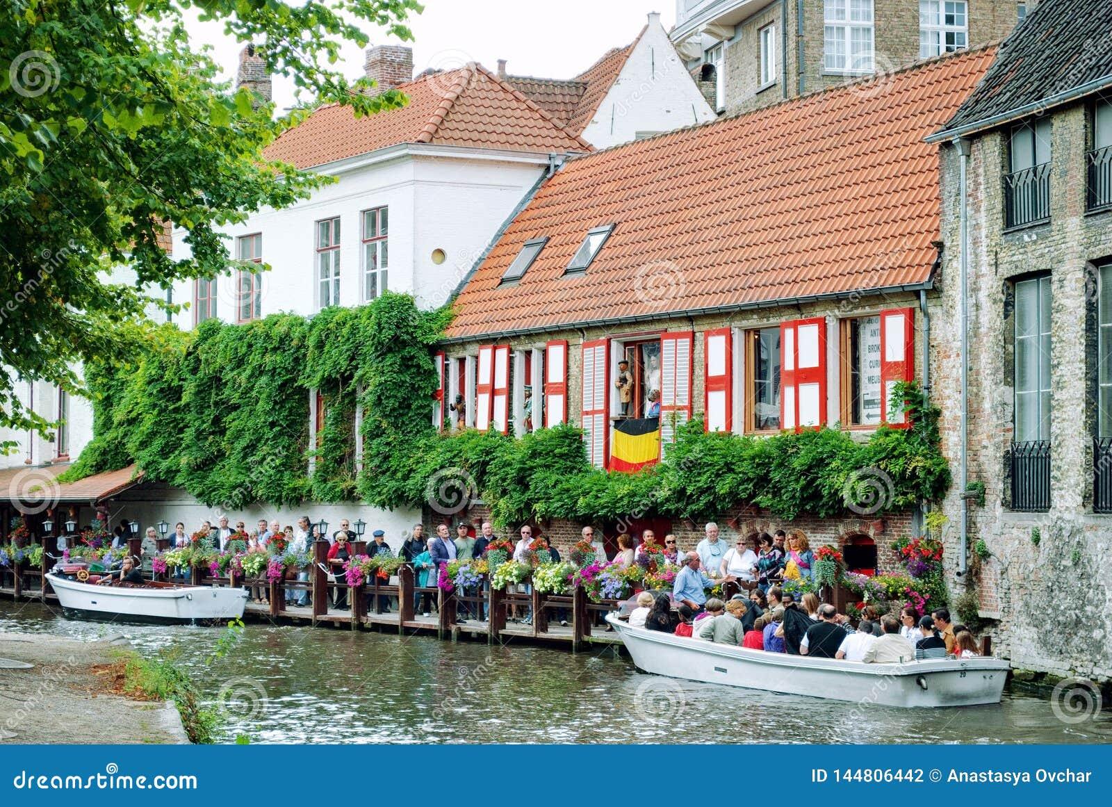 Bruges, Belgio - agosto 2010: Turisti che stanno in una coda sul pilastro per il loro viaggio della barca lungo i canali della ci