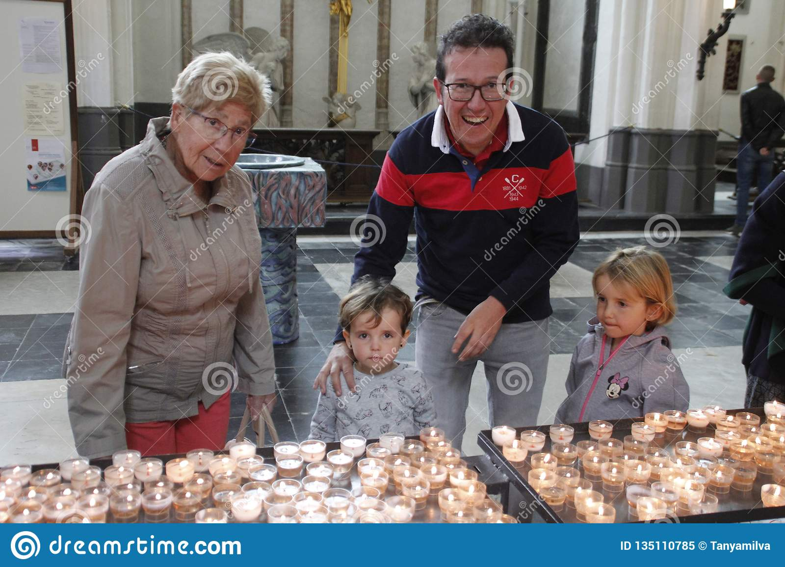 Family: grandmother, father and two little girls sisters light candles inside the church