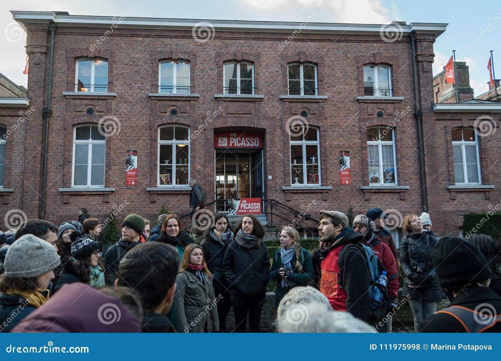 Brugge östliga Flanders/Belgien - Januari 2018: Gå turnerar folket från det behind på fritt gå i Brugge
