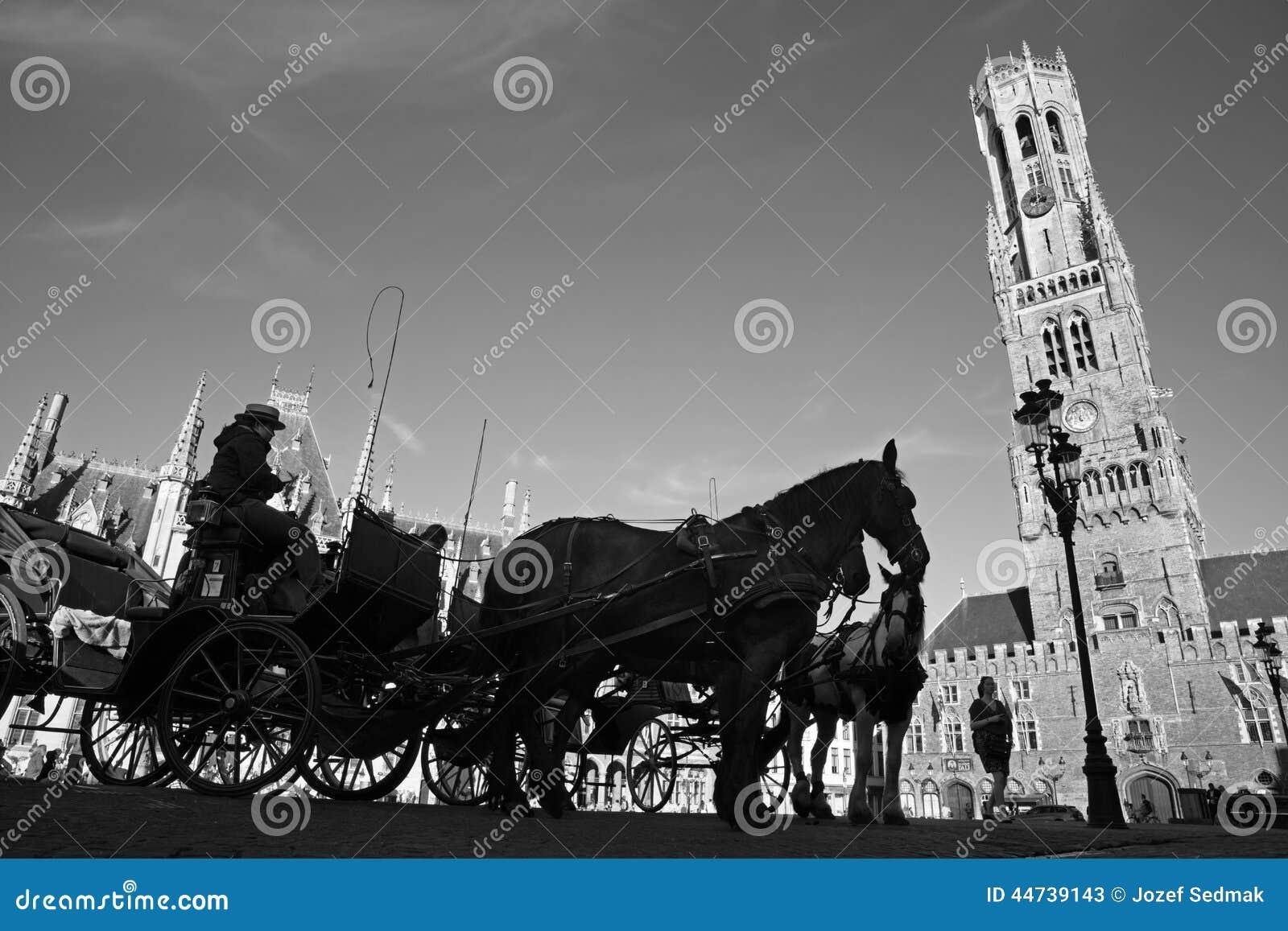 BRUGGE BELGIEN - JUNI 13, 2014: Vagnen på den Grote Markt och Belfort skåpbilen Brugge