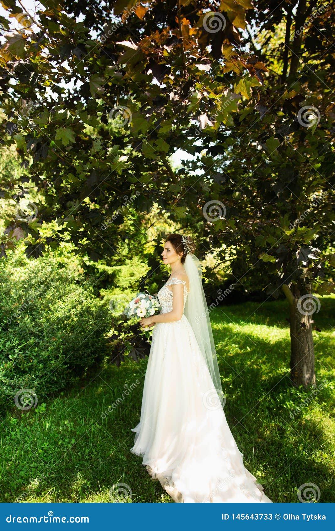 Bruid in de kleding van het manierhuwelijk op natuurlijke achtergrond Een mooi vrouwenportret in het park