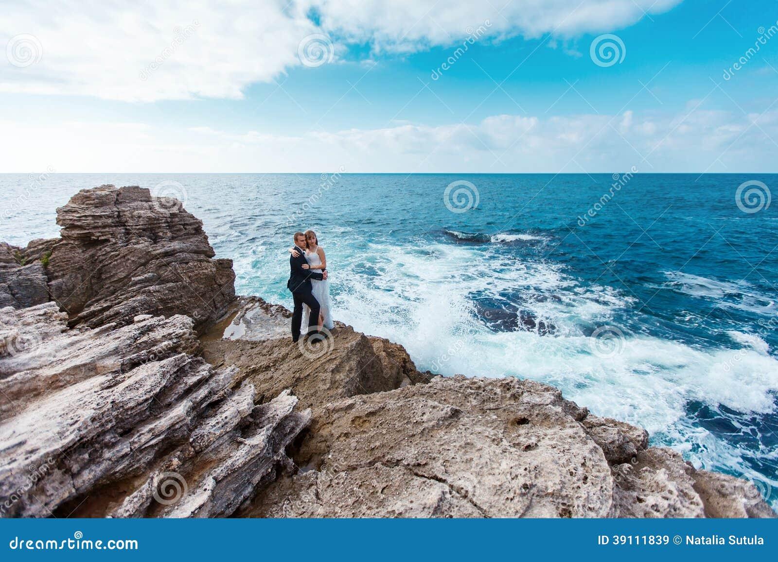 Bruid en bruidegom dichtbij de oceaan