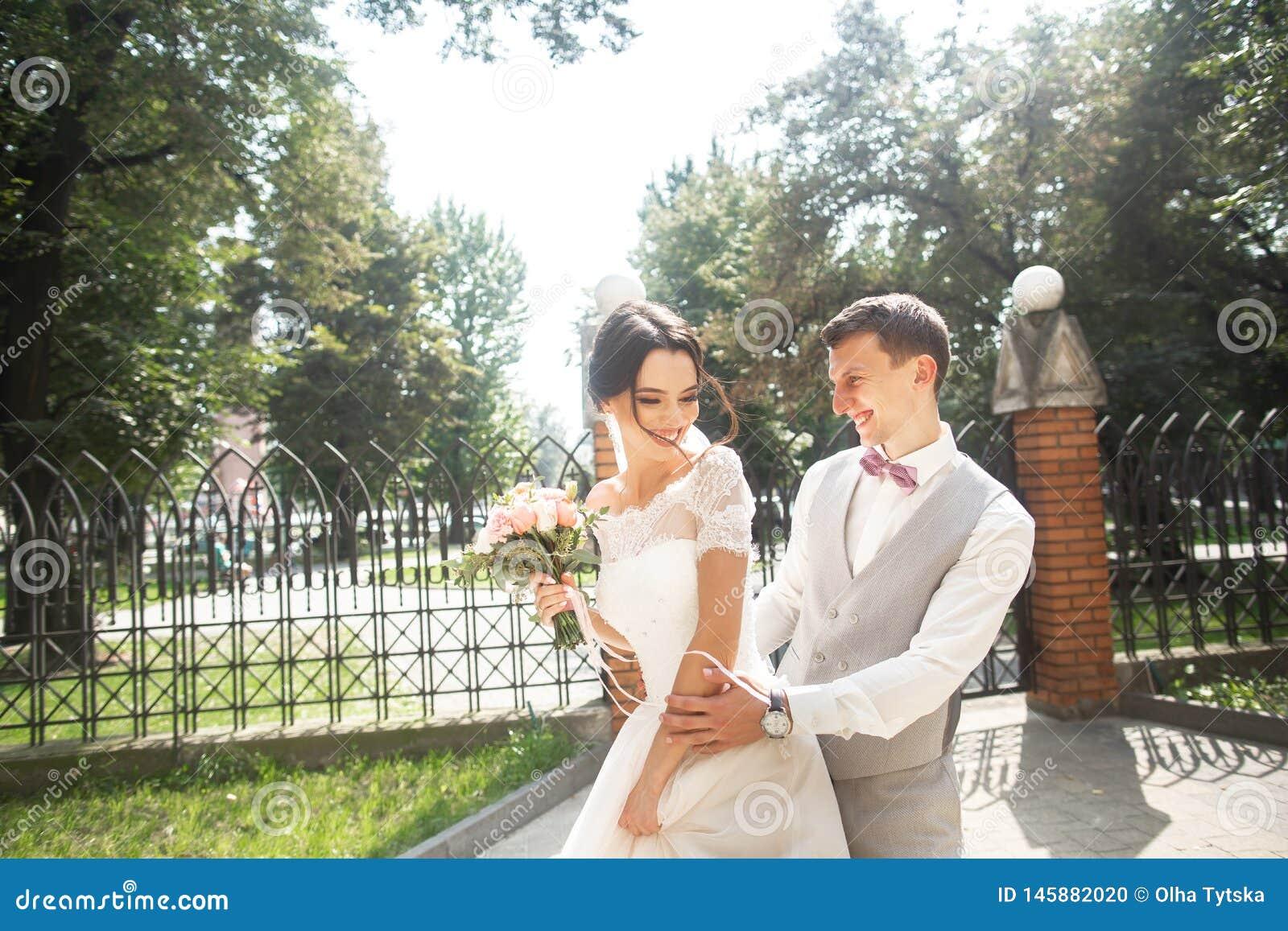 Bruid en bruidegom die bij huwelijksdag in een mooi park, het glimlachen eind lopen die van elkaar genieten