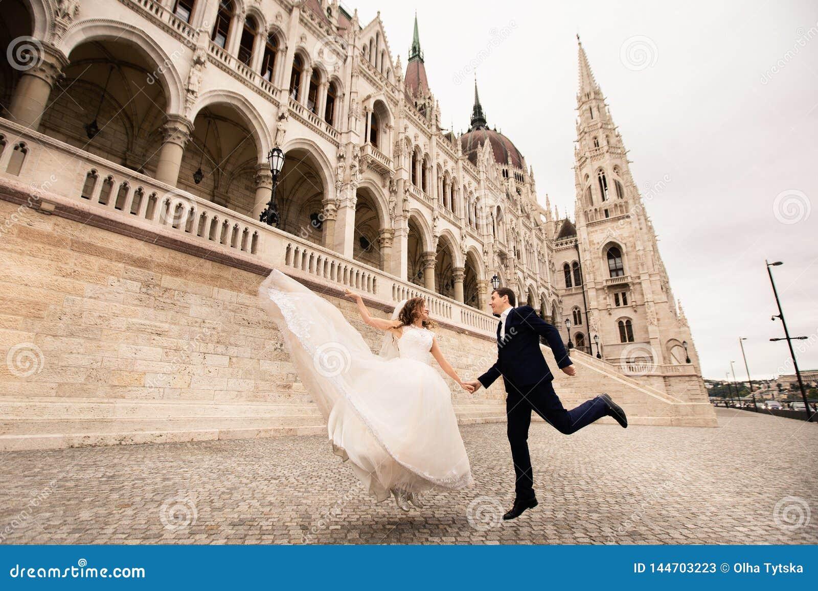 Bruid en bruidegom die in de oude stadsstraat koesteren De gangen van het huwelijkspaar in Boedapest dichtbij het Parlement Huis