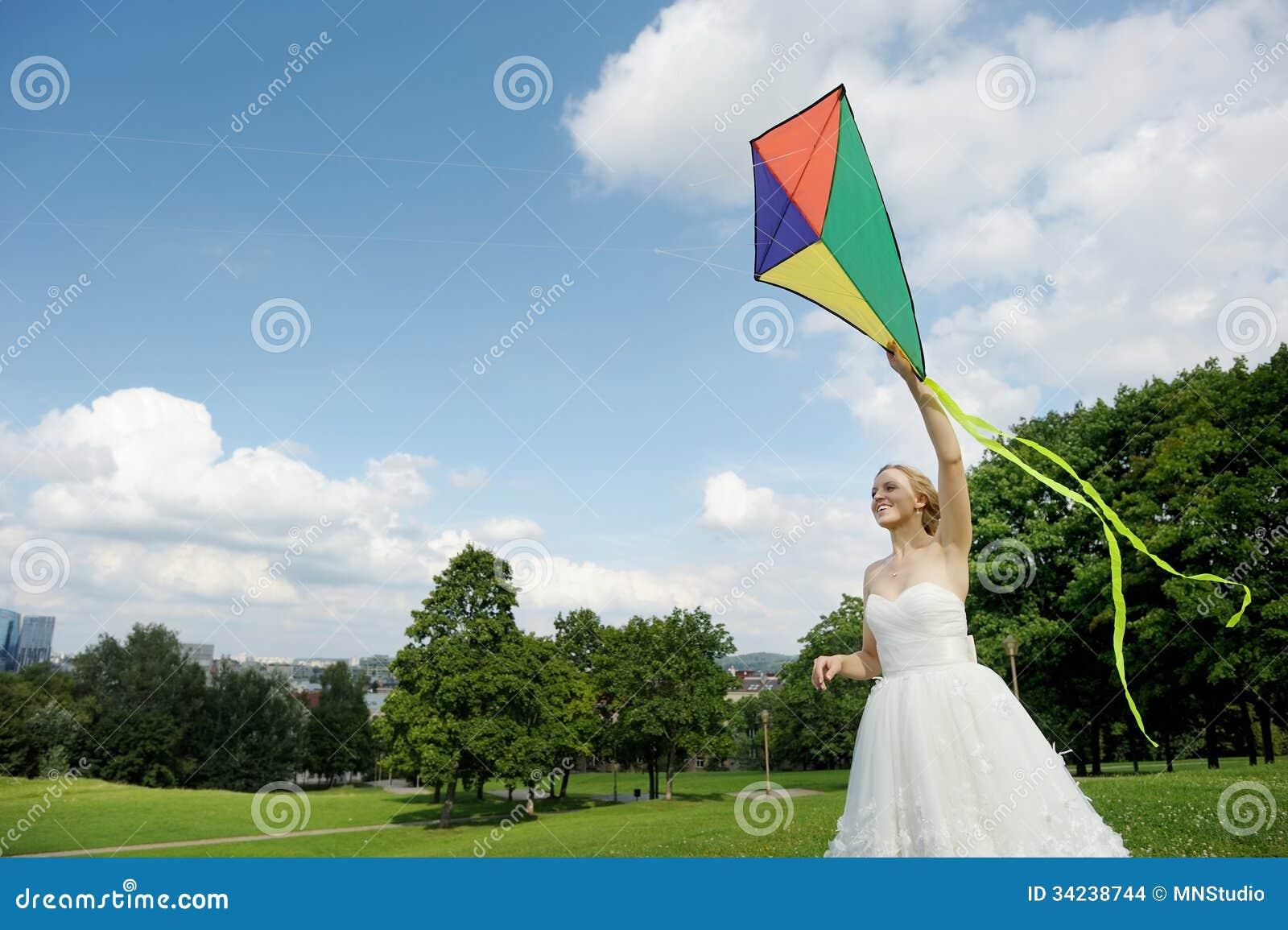 Bruid en bruidegom die een vlieger op een huwelijksdag vliegen