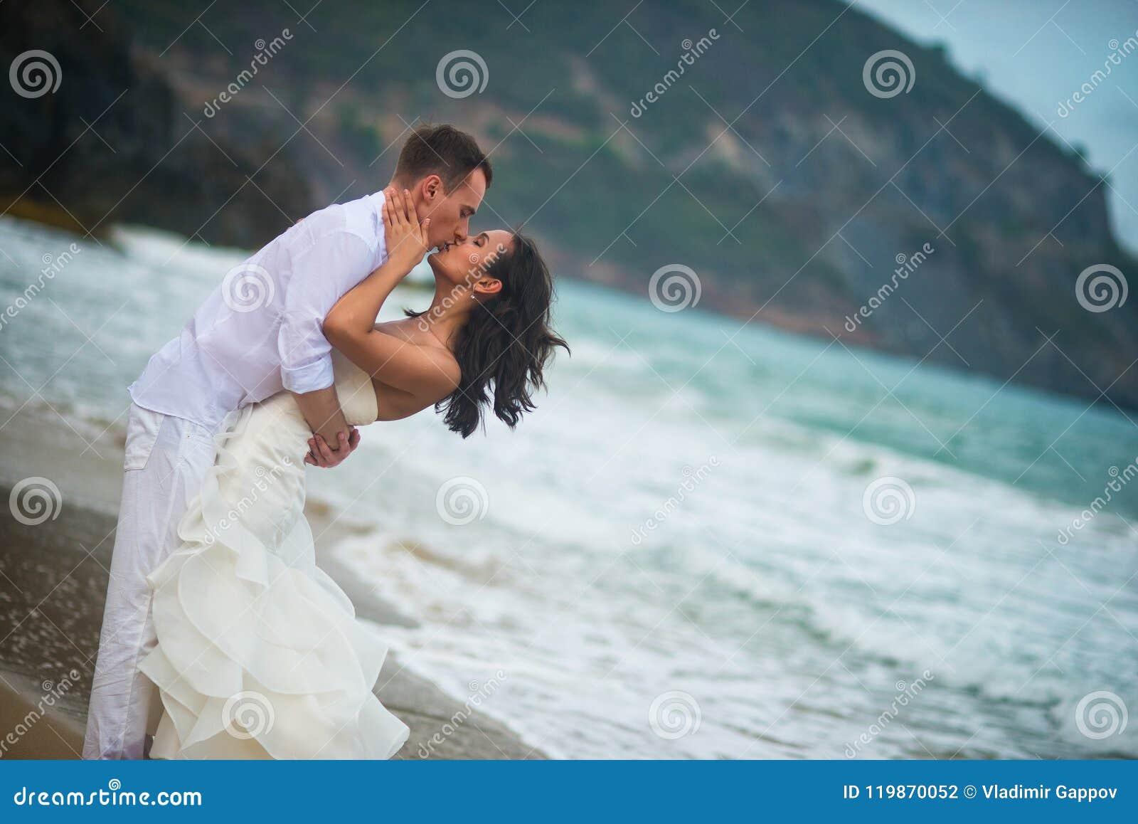 Bruid en bruidegom het kussen door het overzees paar in liefde op een verlaten strand