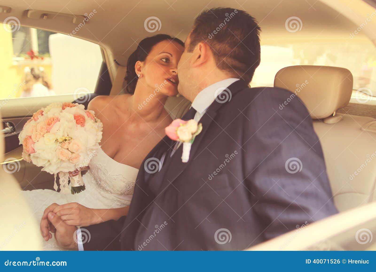 Bruid en bruidegom in huwelijksauto