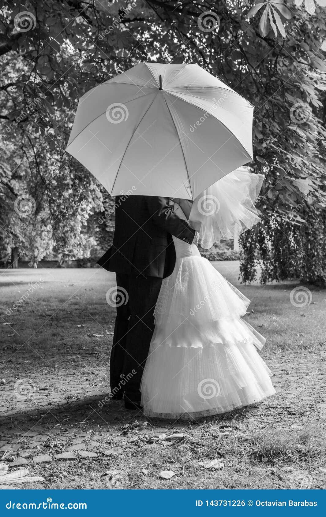 Bruid en bruidegom met witte paraplu