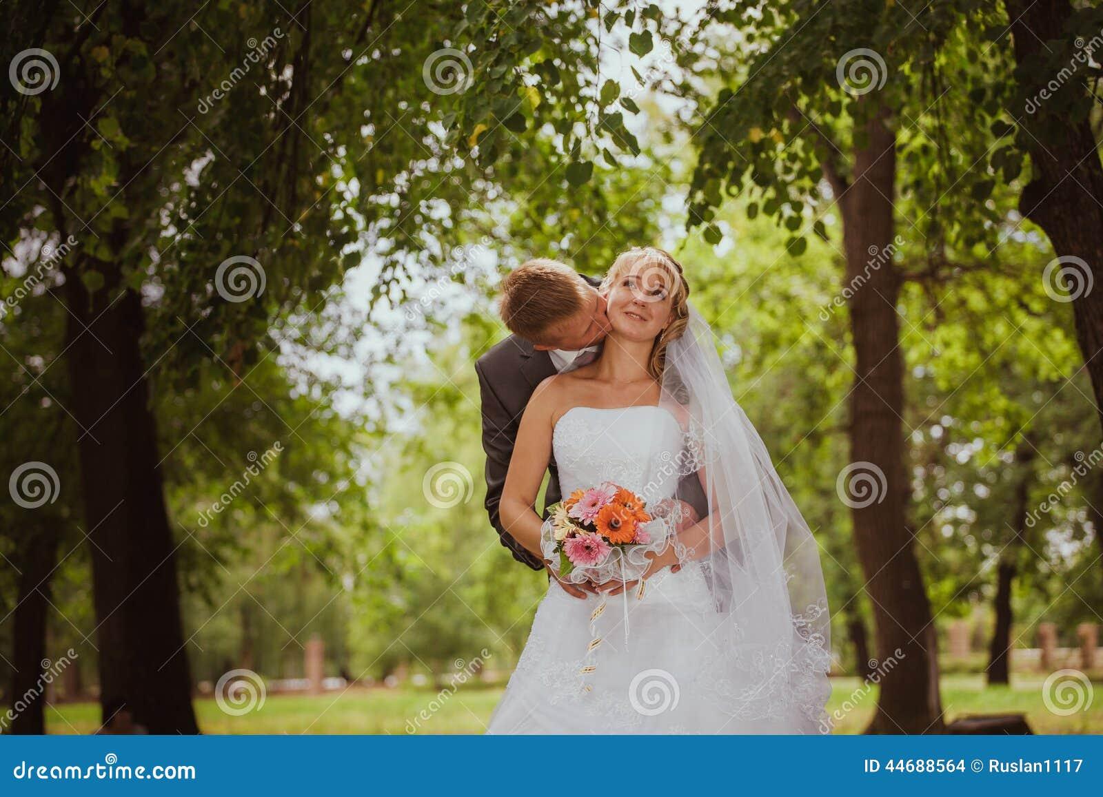 Bruid en bruidegom in park het kussen de bruid en de bruidegom van paarjonggehuwden bij een huwelijk in aard groen bos kussen fot