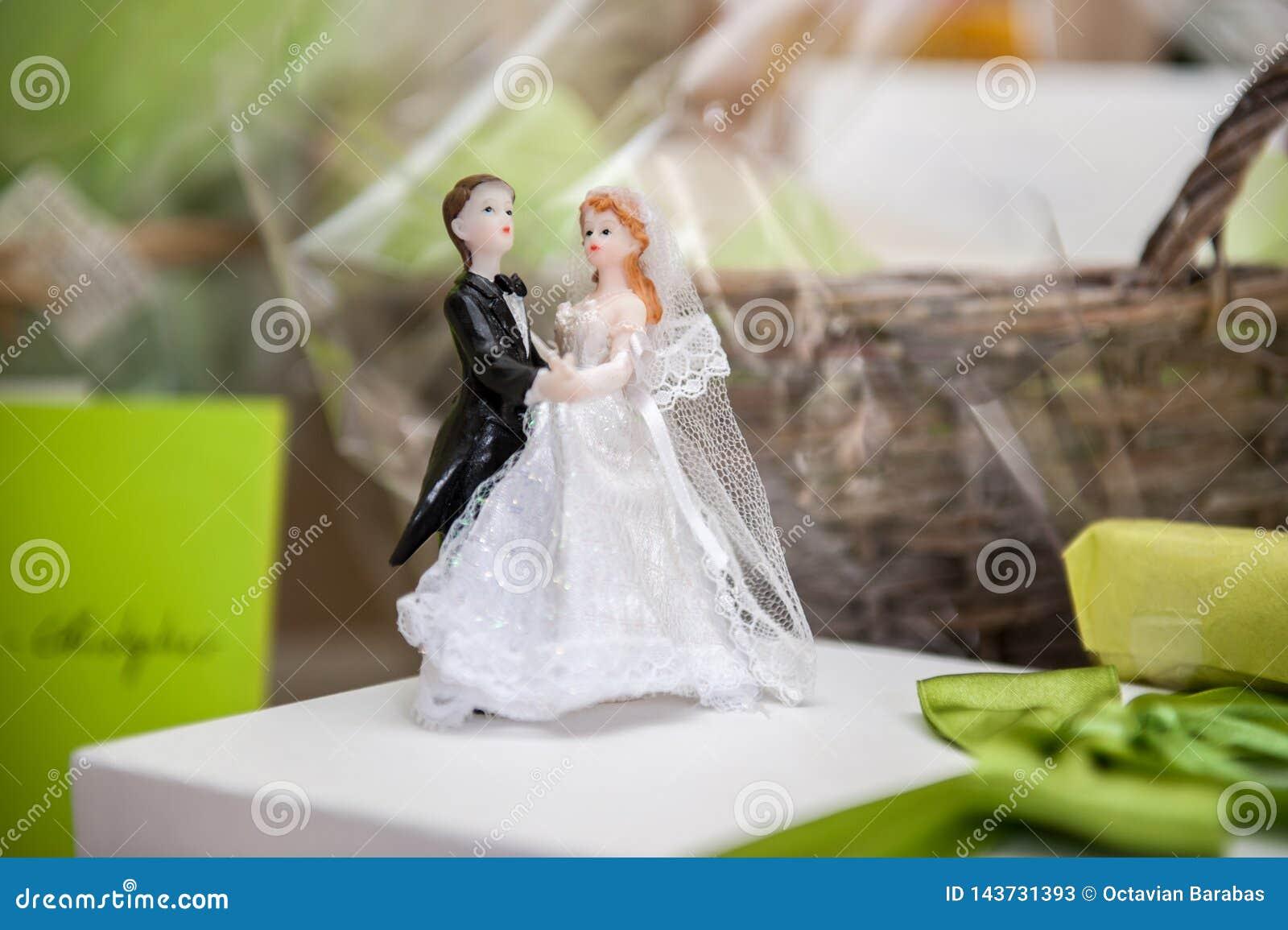 Bruid en bruidegom van suiker bovenop huwelijkscake die wordt gemaakt